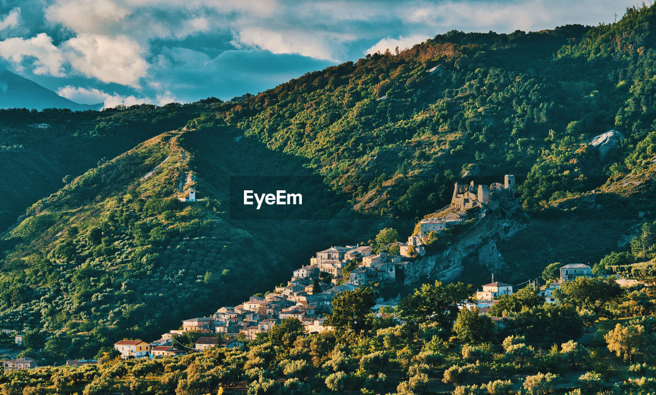 mountain, scenics - nature, beauty in nature, sky, cloud - sky, nature, architecture, no people, tranquil scene, mountain range, day, building exterior, landscape, built structure, environment, tree, building, city, tranquility, green color, outdoors, townscape
