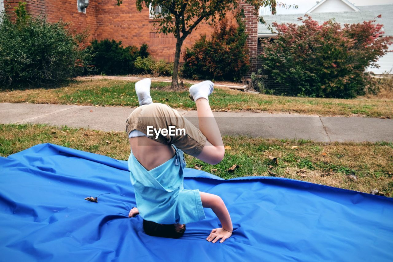 Boy Practicing Handstand On Blue Fabric At Grassy Field Against Sky