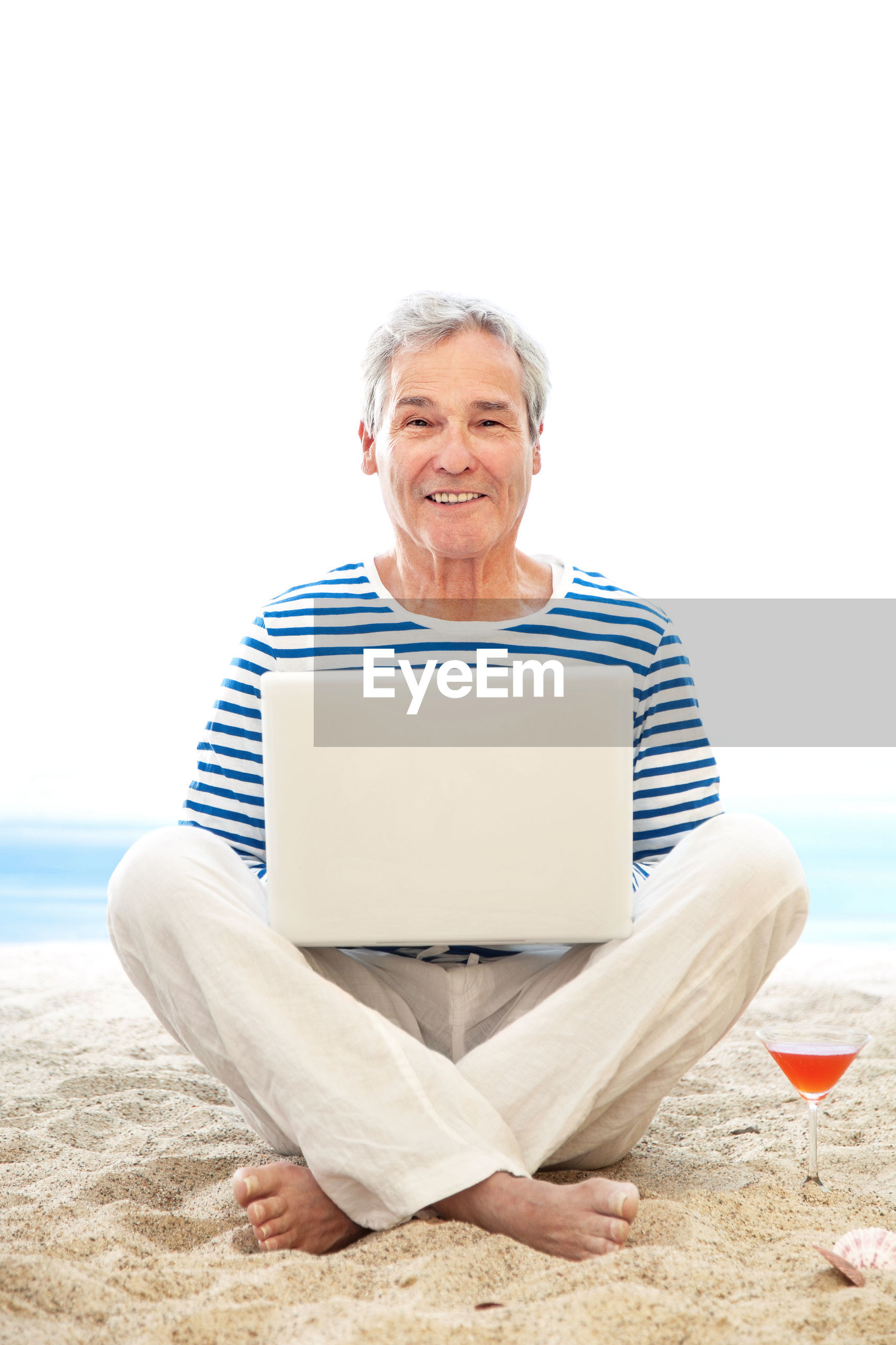 Portrait of man using laptop at beach against sky
