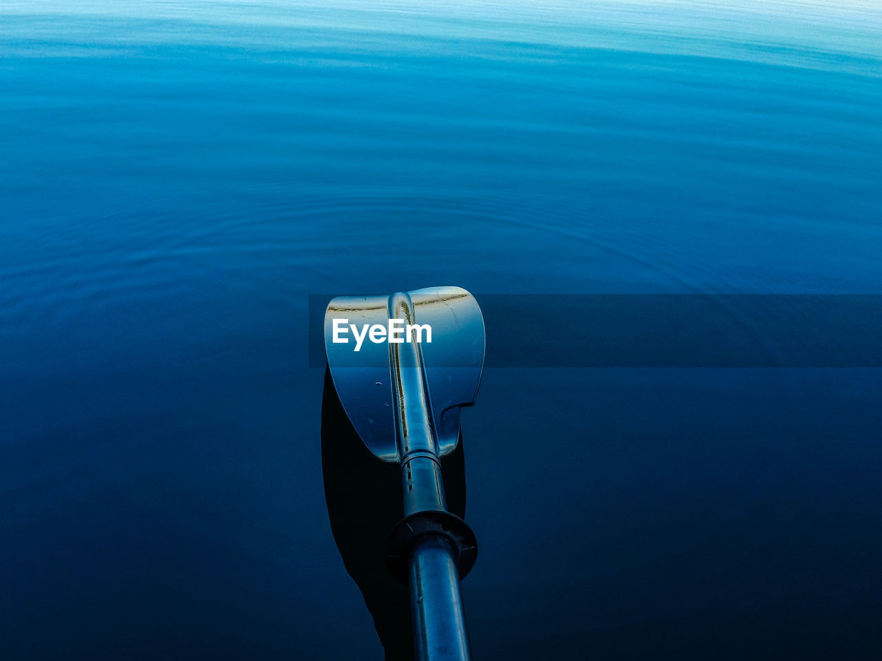 Close-Up Of Oar Above Blue Sea
