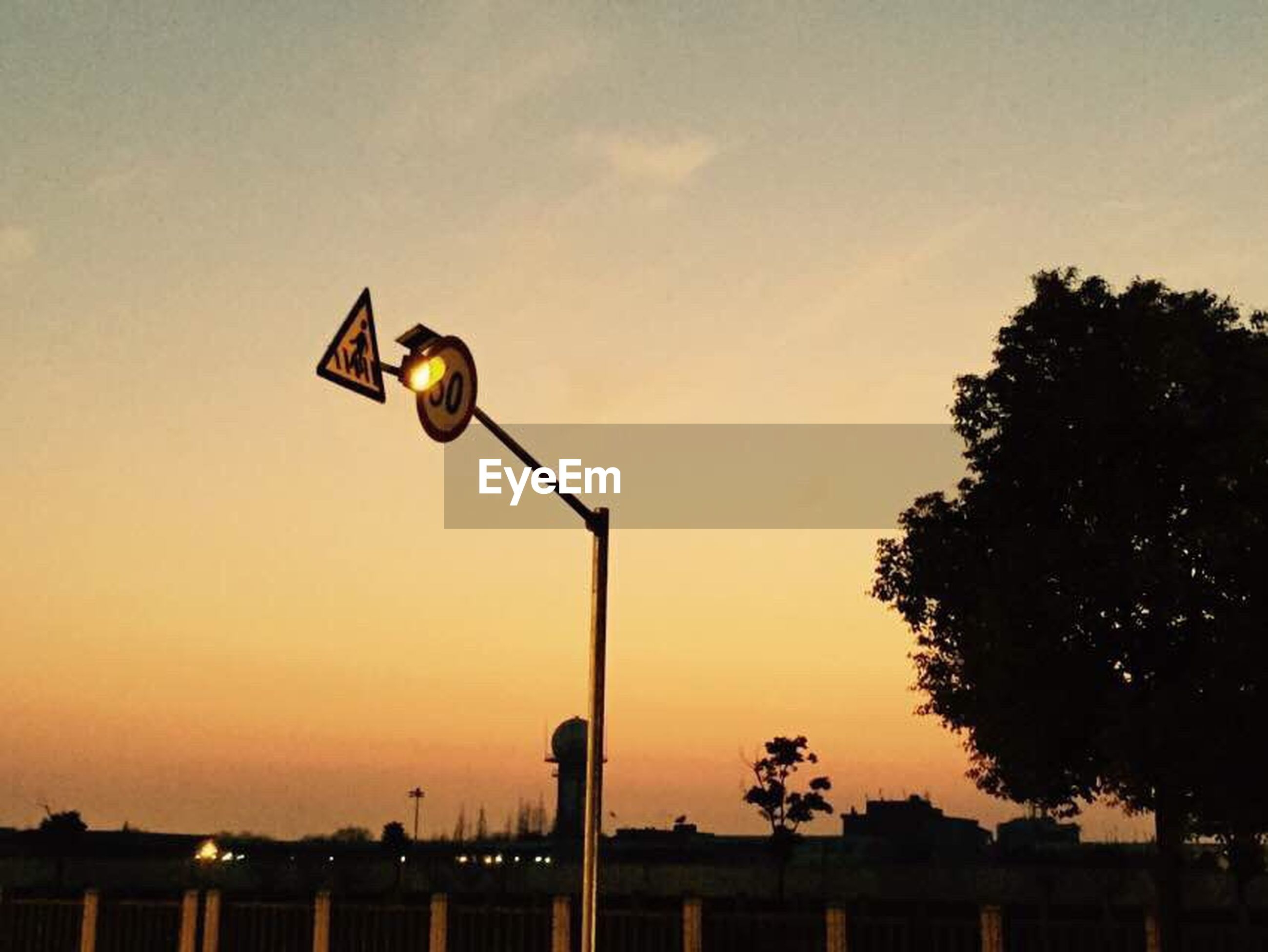 street light, sunset, lighting equipment, sky, silhouette, low angle view, tree, illuminated, orange color, dusk, lamp post, electric light, nature, outdoors, electricity, scenics, no people, tranquility, built structure, beauty in nature