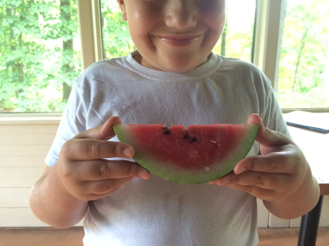 Midsection of happy boy holding watermelon slice at home