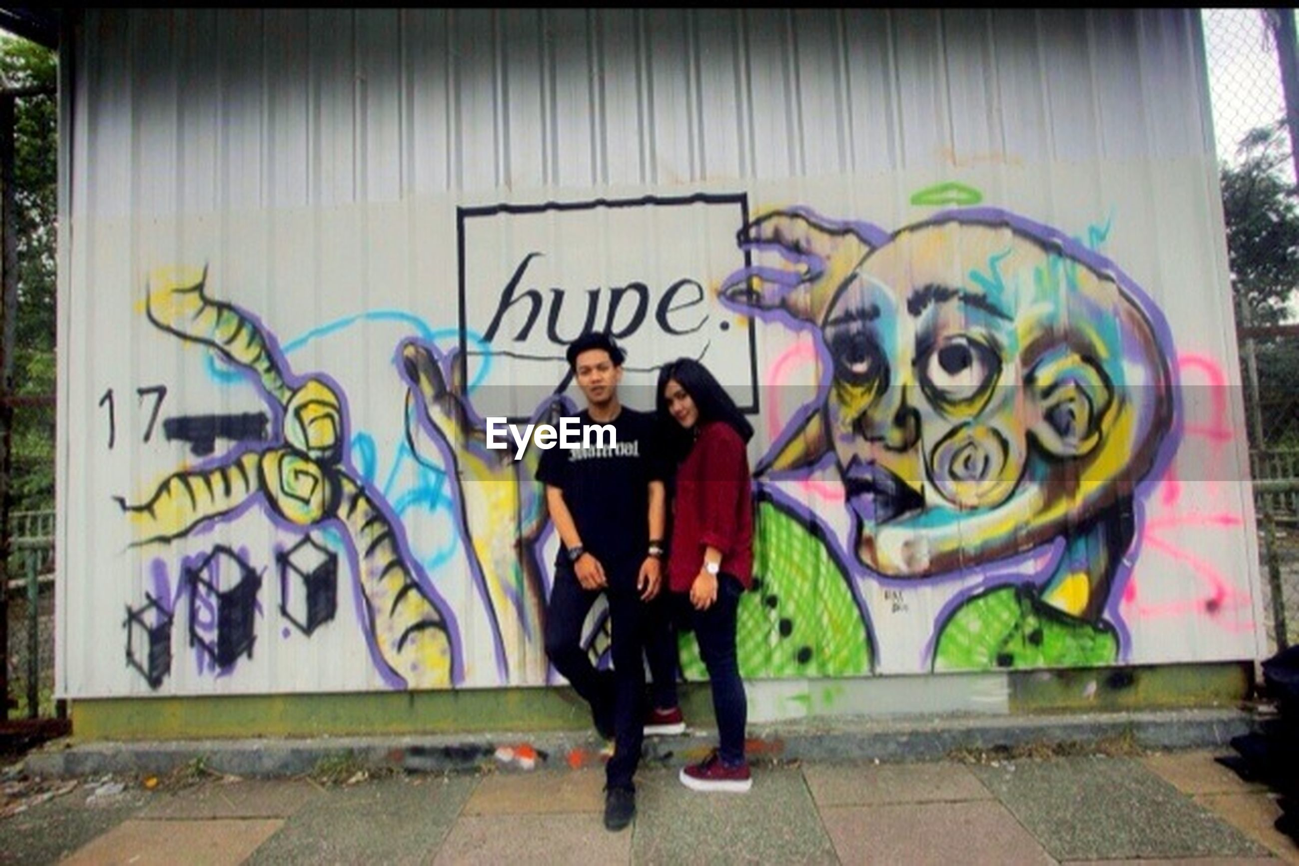 graffiti, art, creativity, art and craft, text, lifestyles, human representation, full length, wall - building feature, built structure, architecture, leisure activity, street, building exterior, western script, communication, street art