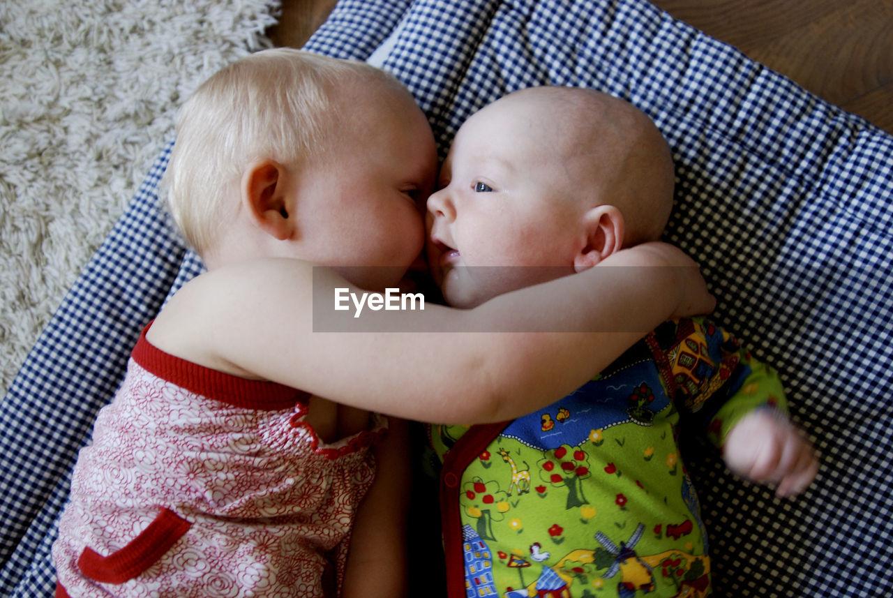 High Angle View Of Siblings Lying On Fabric
