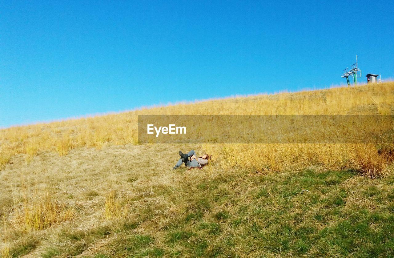 Woman lying on field against clear blue sky