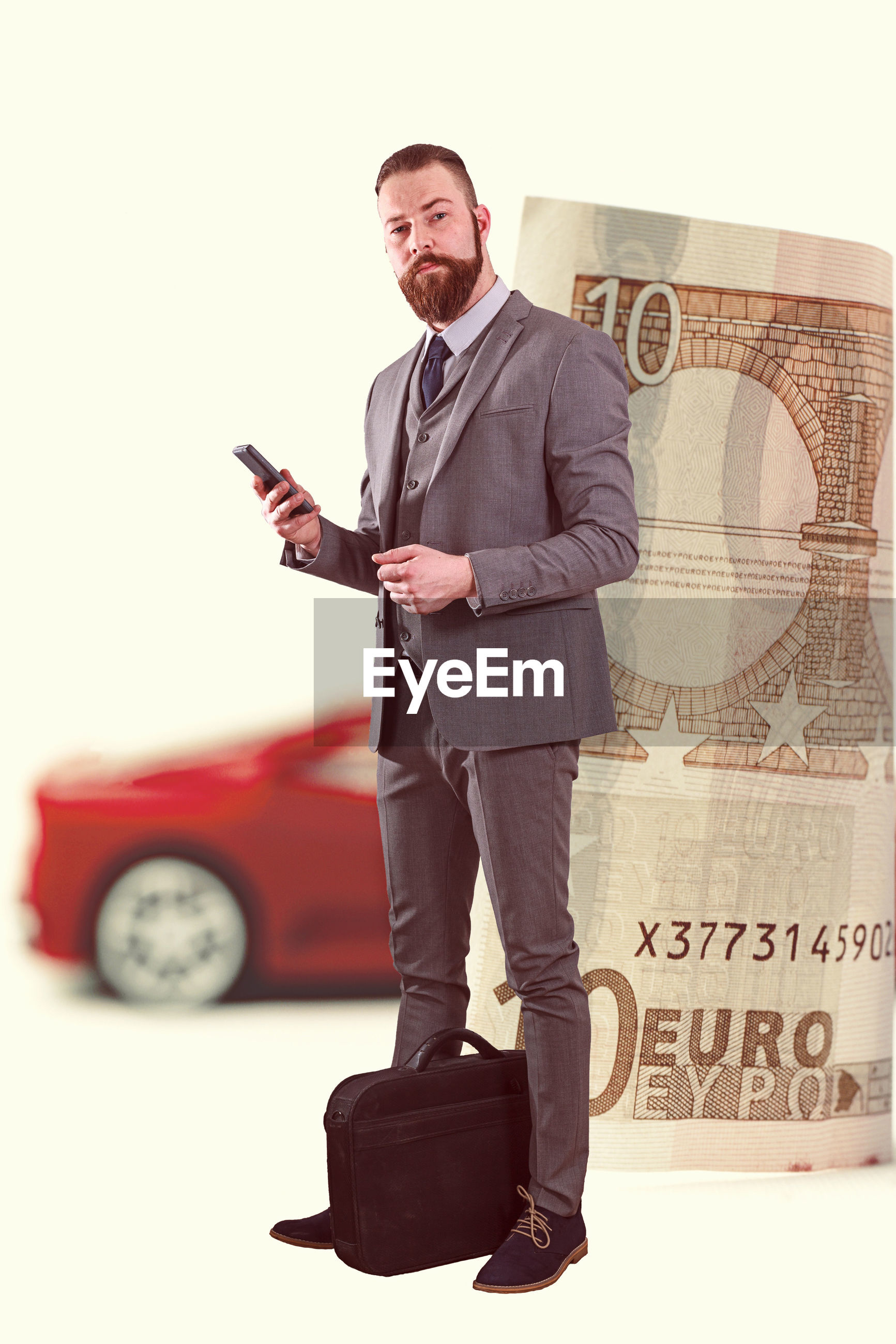 Portrait of businessman standing by paper currency and toy car over white background