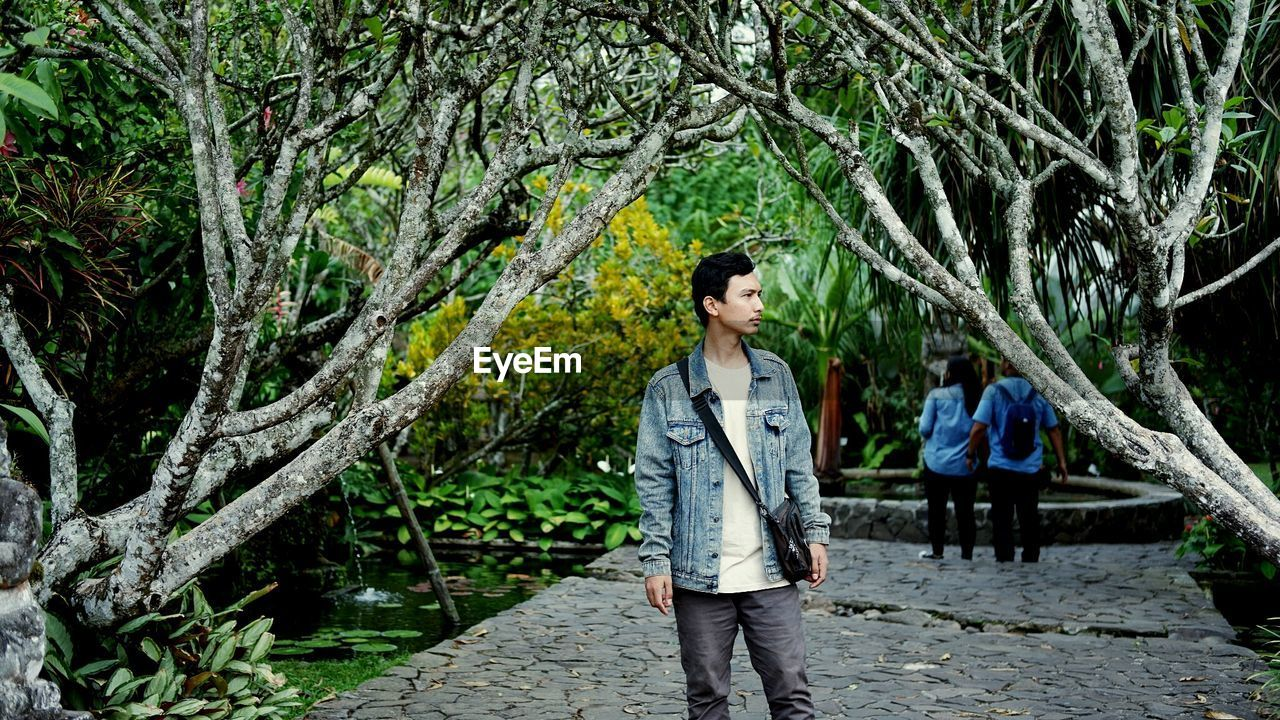 Thoughtful young man standing amidst bare branches