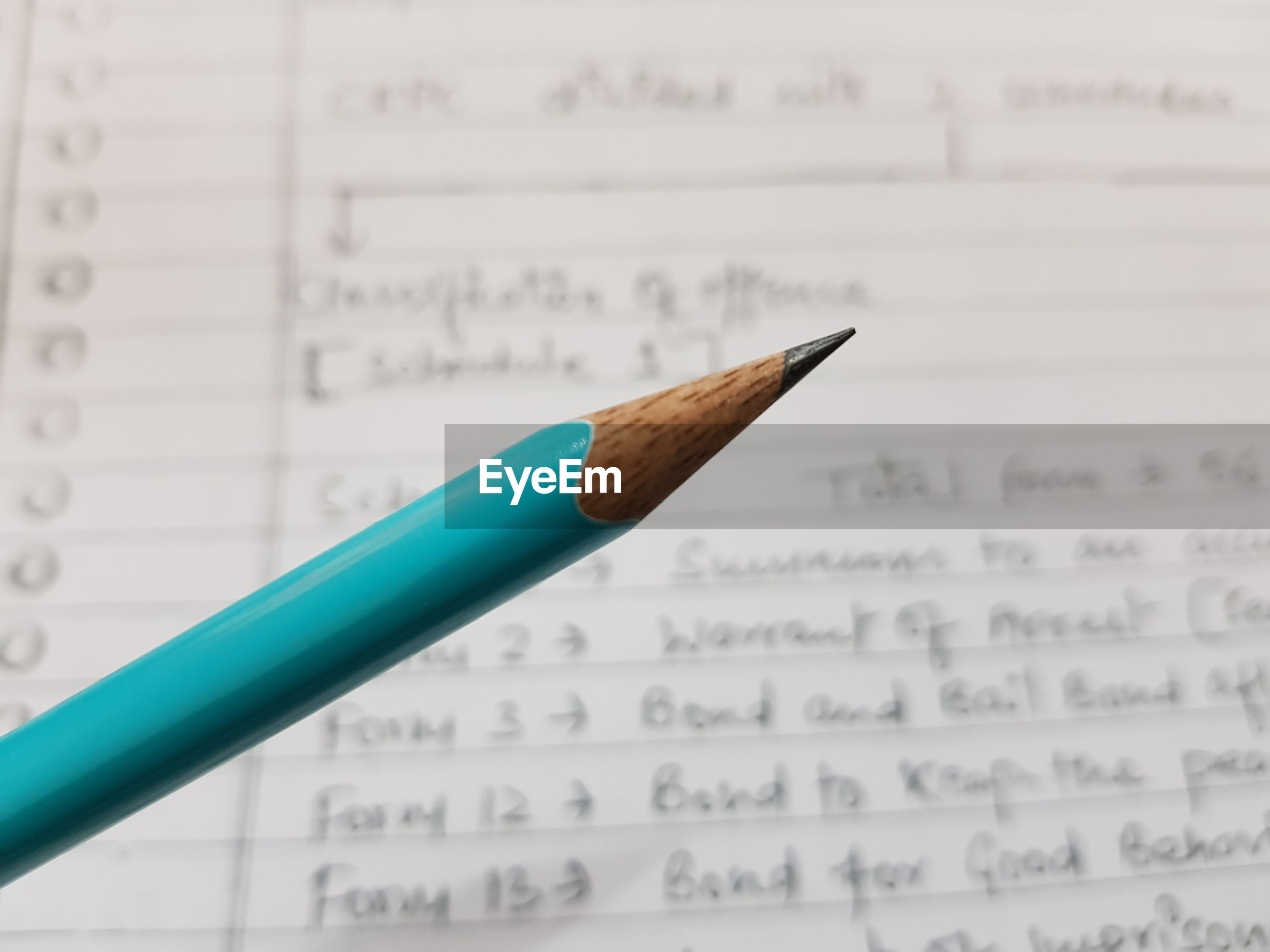 Close-up of pencil over book