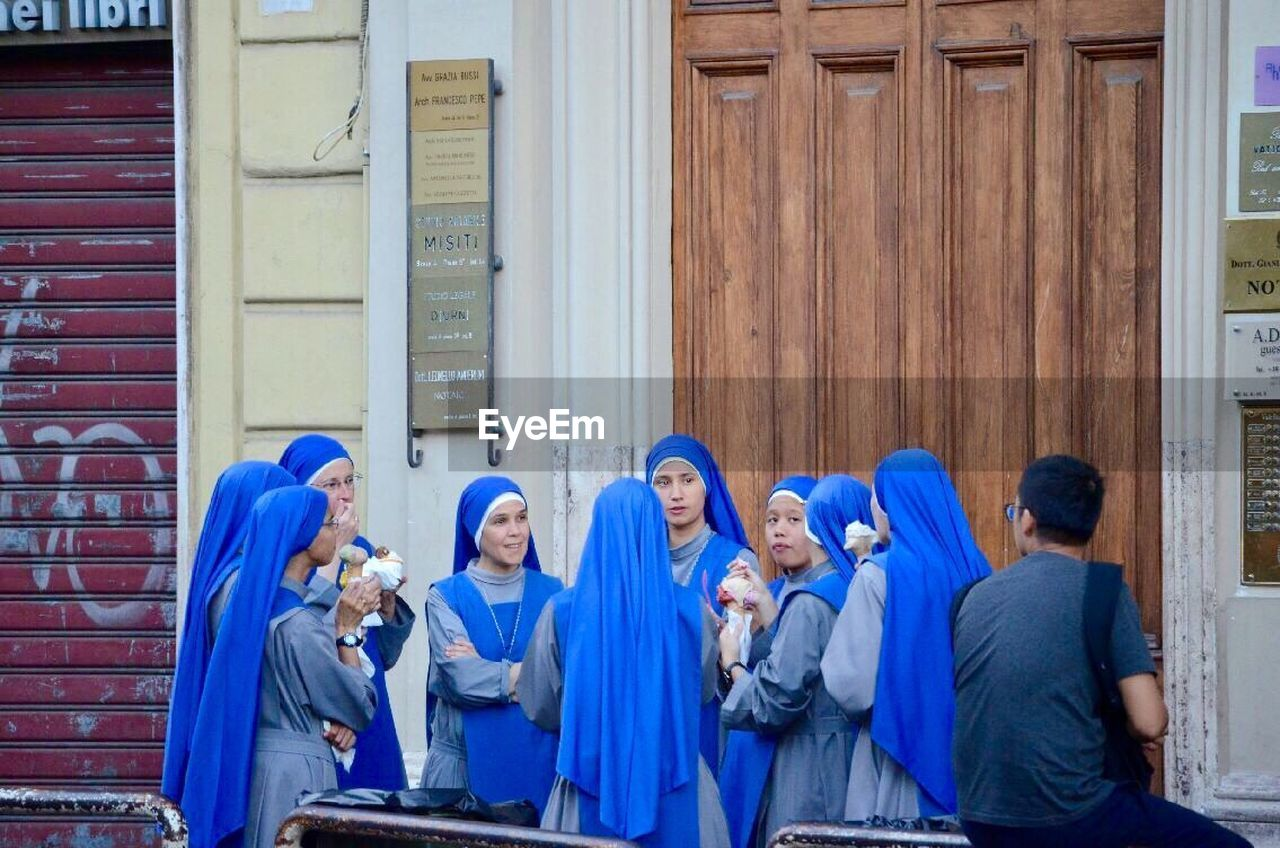 young men, togetherness, building exterior, young adult, day, mature women, mature adult, men, medium group of people, young women, women, real people, outdoors, hooded shirt, blue, candid, friendship, standing, adult, community, architecture, people, adults only