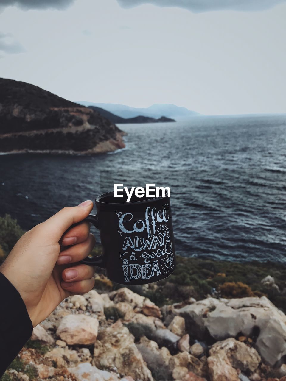 Cropped hand holding coffee cup at beach