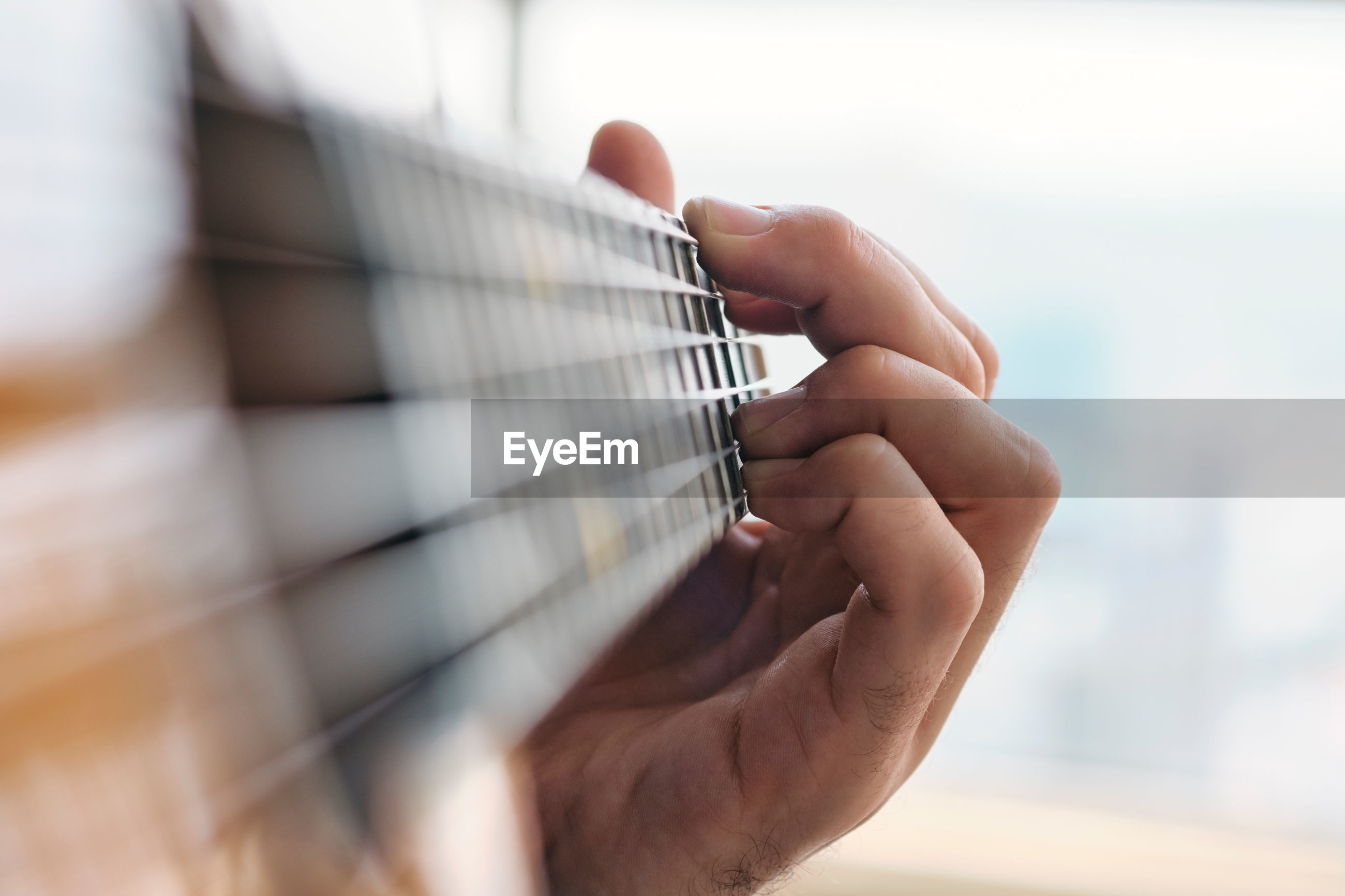 Close-up of hand playing guitar at home