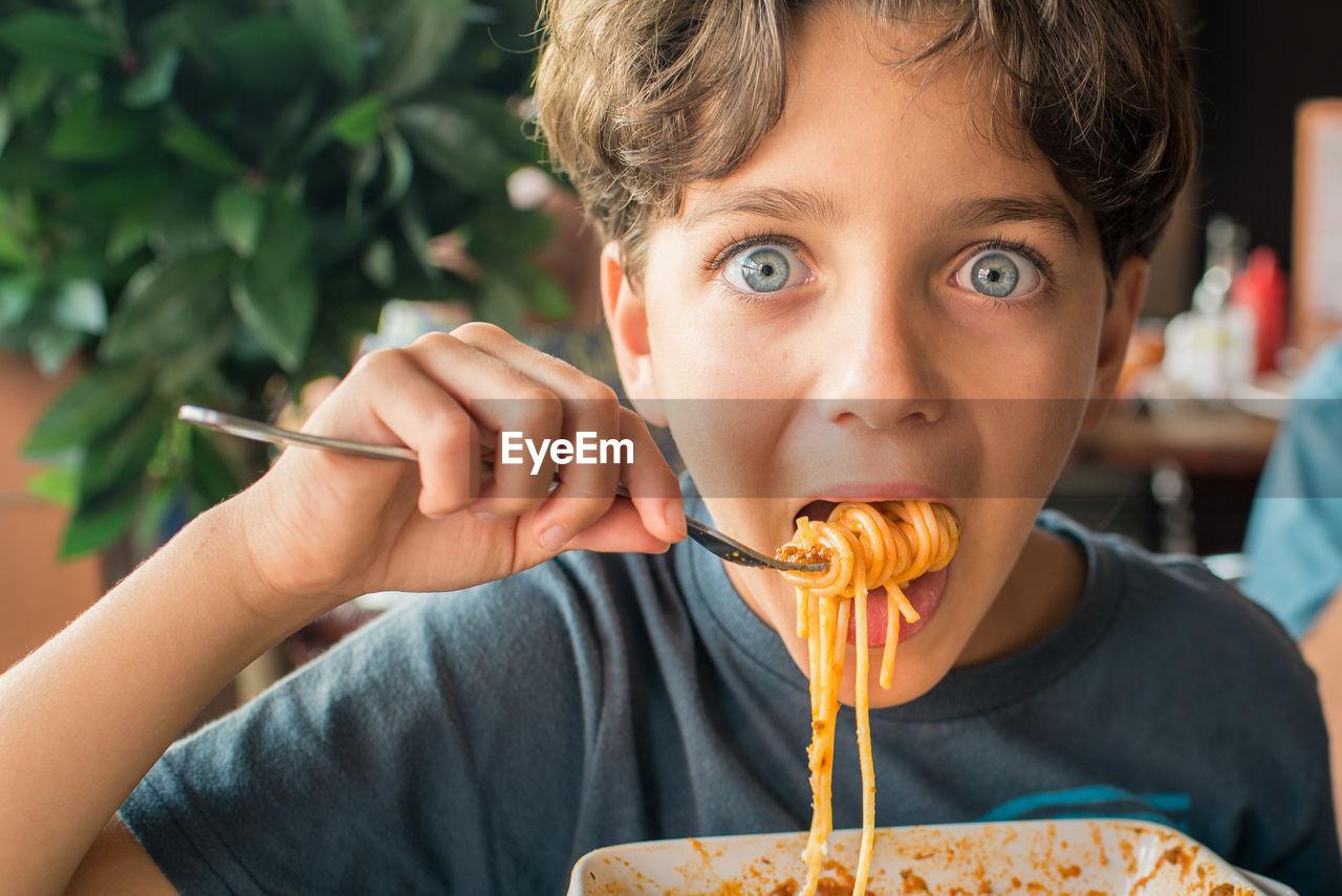 Close-Up Portrait Of Boy Eating Noodles