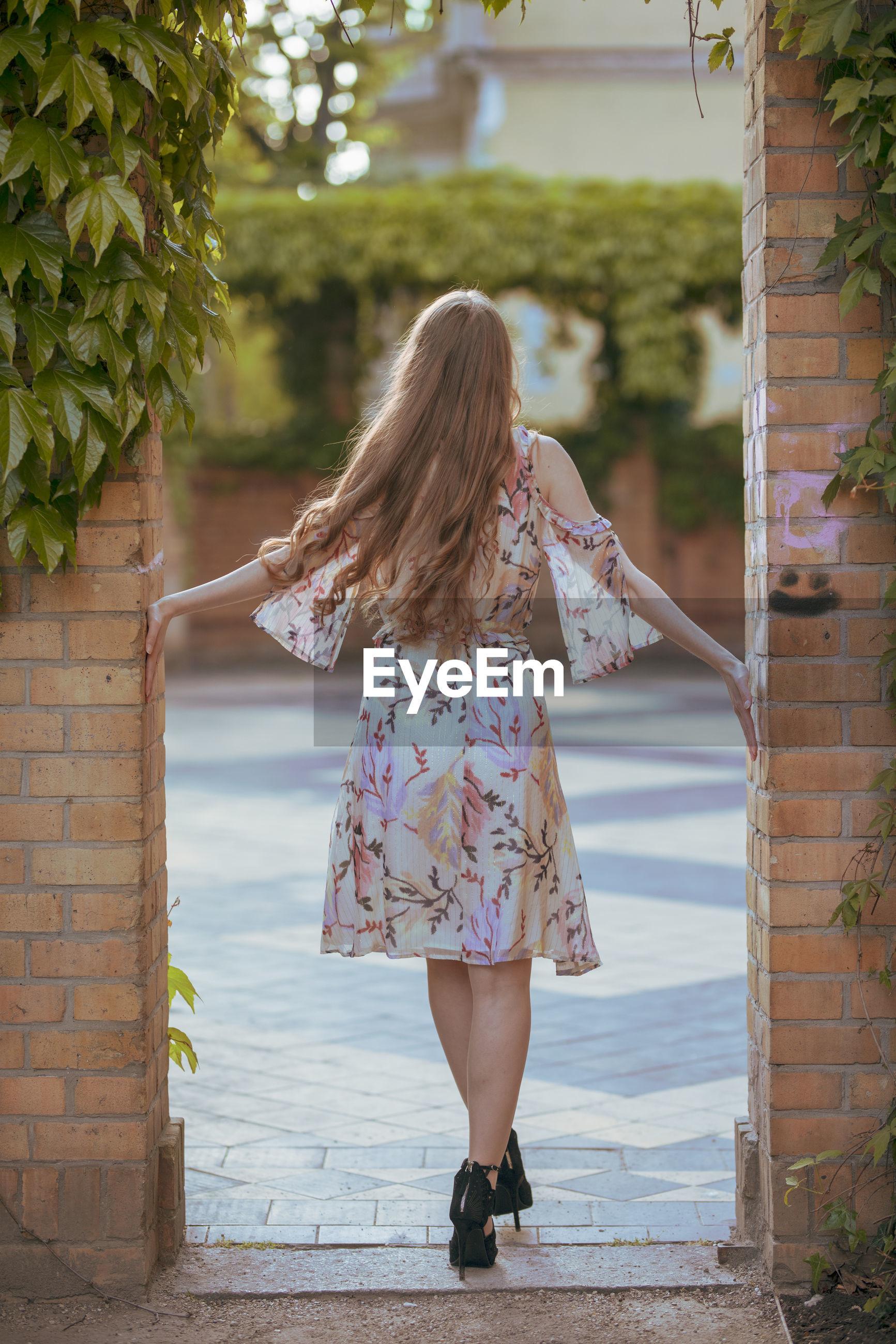Rear view of woman walking at doorway in park