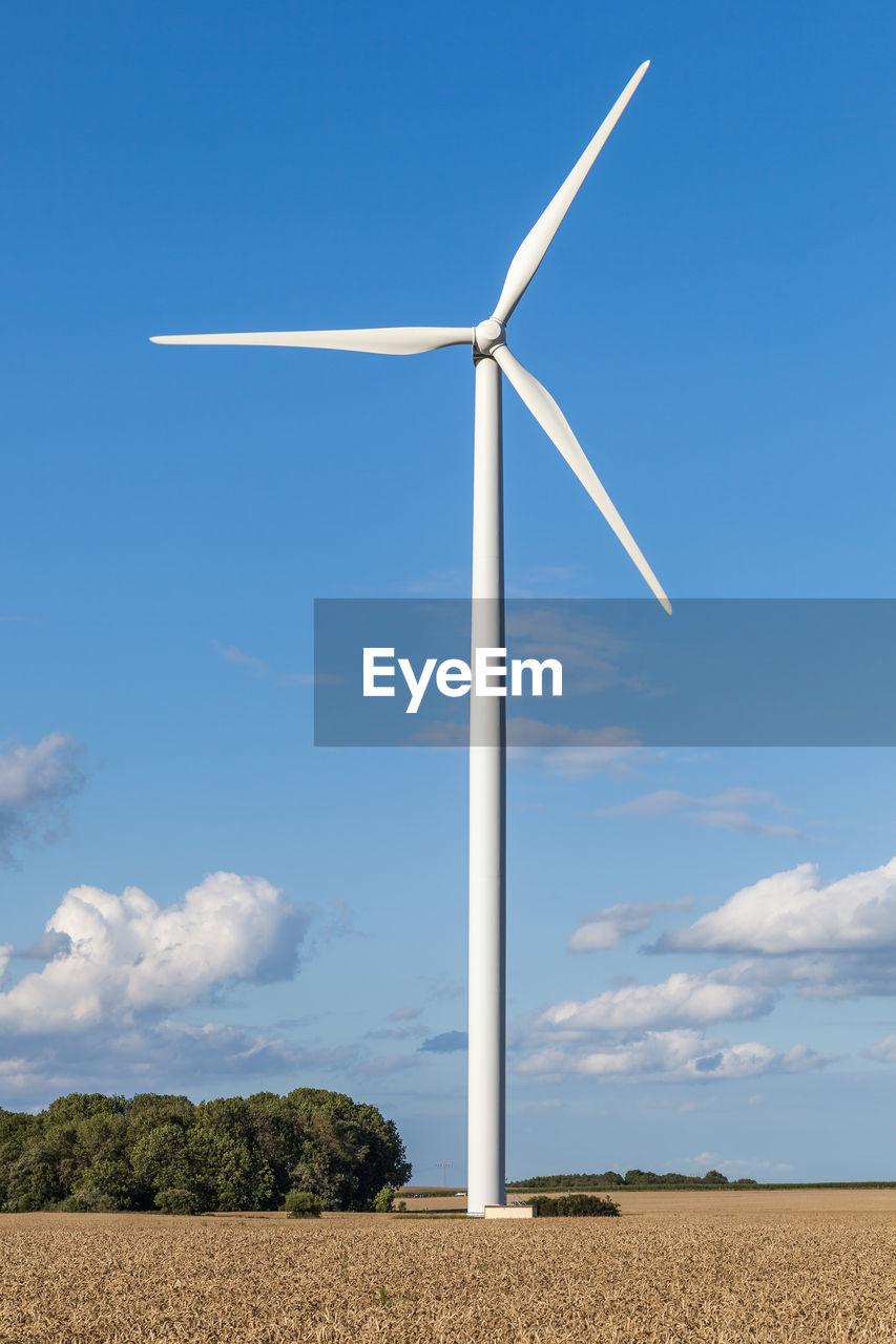 Wind Turbine On Field Against Blue Sky