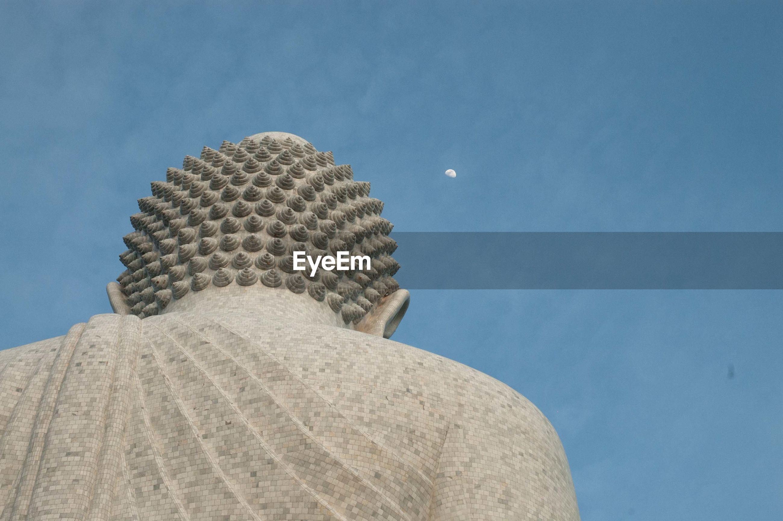 Low angle view of buddha statue against sky at dusk