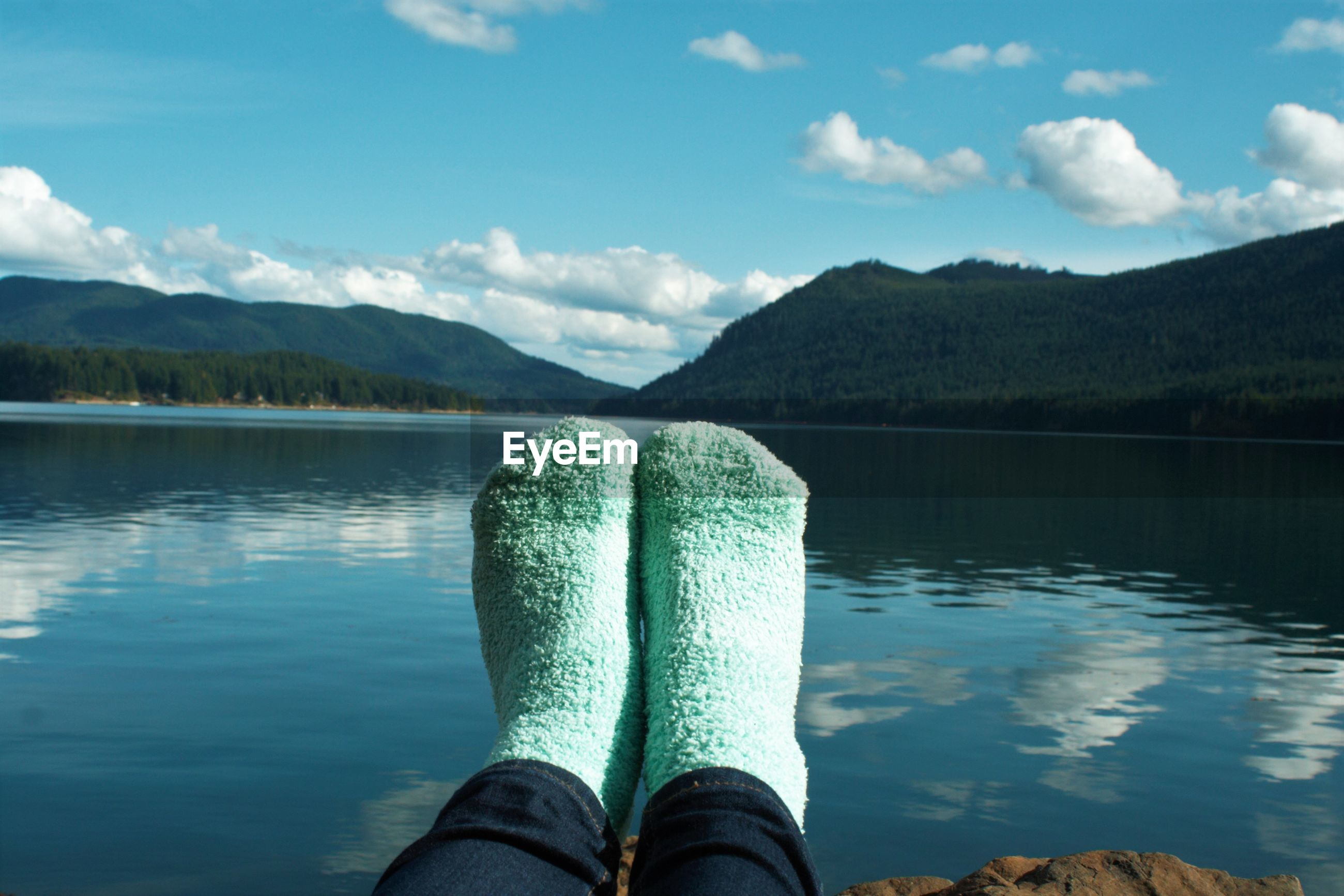 Low section of person wearing socks by lake against sky