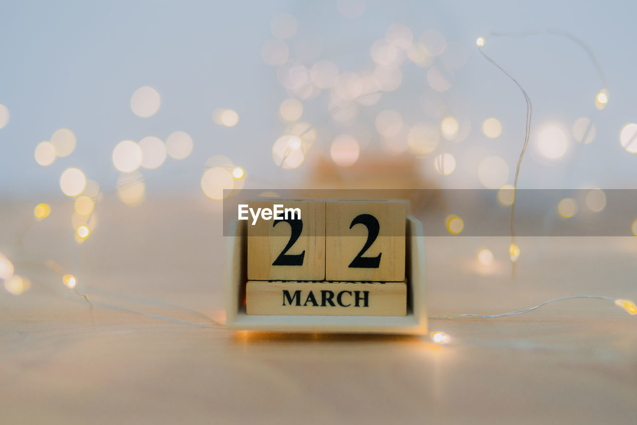 Close-up of march date with illuminated string lights on table