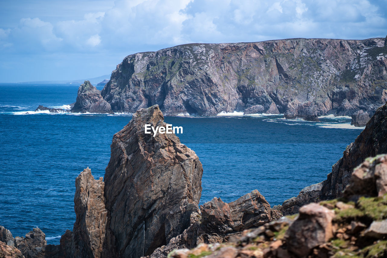 sea, rock, sky, water, rock - object, beauty in nature, scenics - nature, solid, horizon, rock formation, nature, land, day, tranquil scene, cliff, tranquility, horizon over water, mountain, no people, outdoors, formation, rocky coastline, eroded