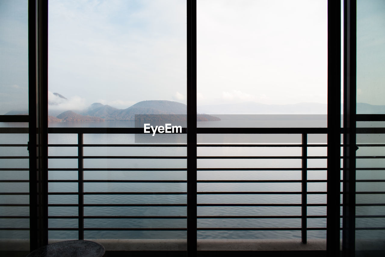 window, glass - material, transparent, mountain, indoors, no people, day, sky, nature, mountain range, architecture, cloud - sky, beauty in nature, table, scenics - nature, water, metal, railing, window frame