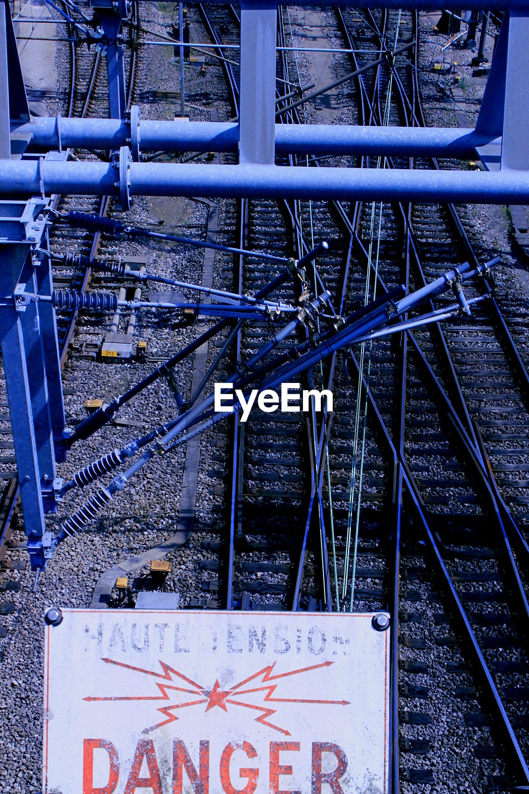 text, western script, metal, communication, transportation, railing, day, high angle view, information sign, no people, metallic, outdoors, capital letter, sign, mode of transport, warning sign, tree, rail transportation, railroad track, number