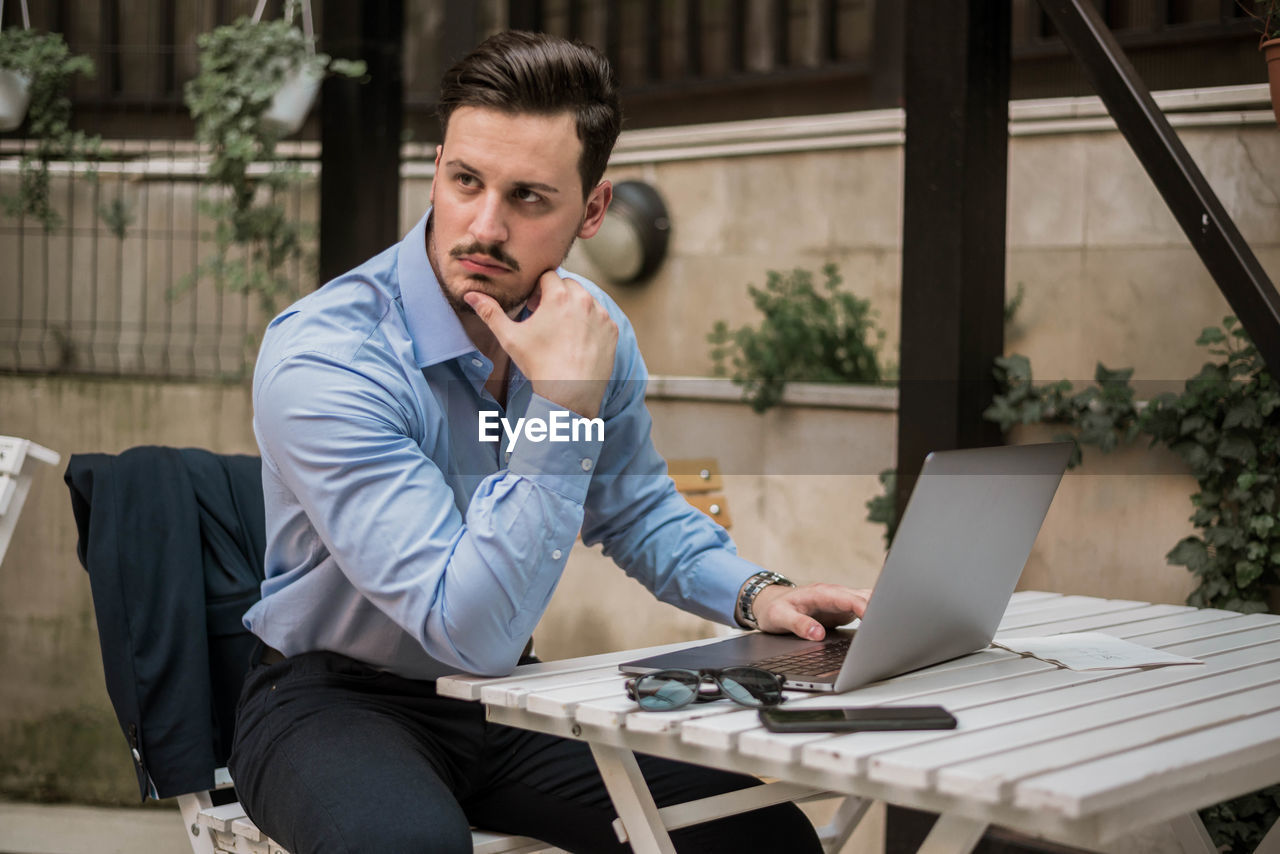 Thoughtful businessman using laptop while sitting on table outdoors
