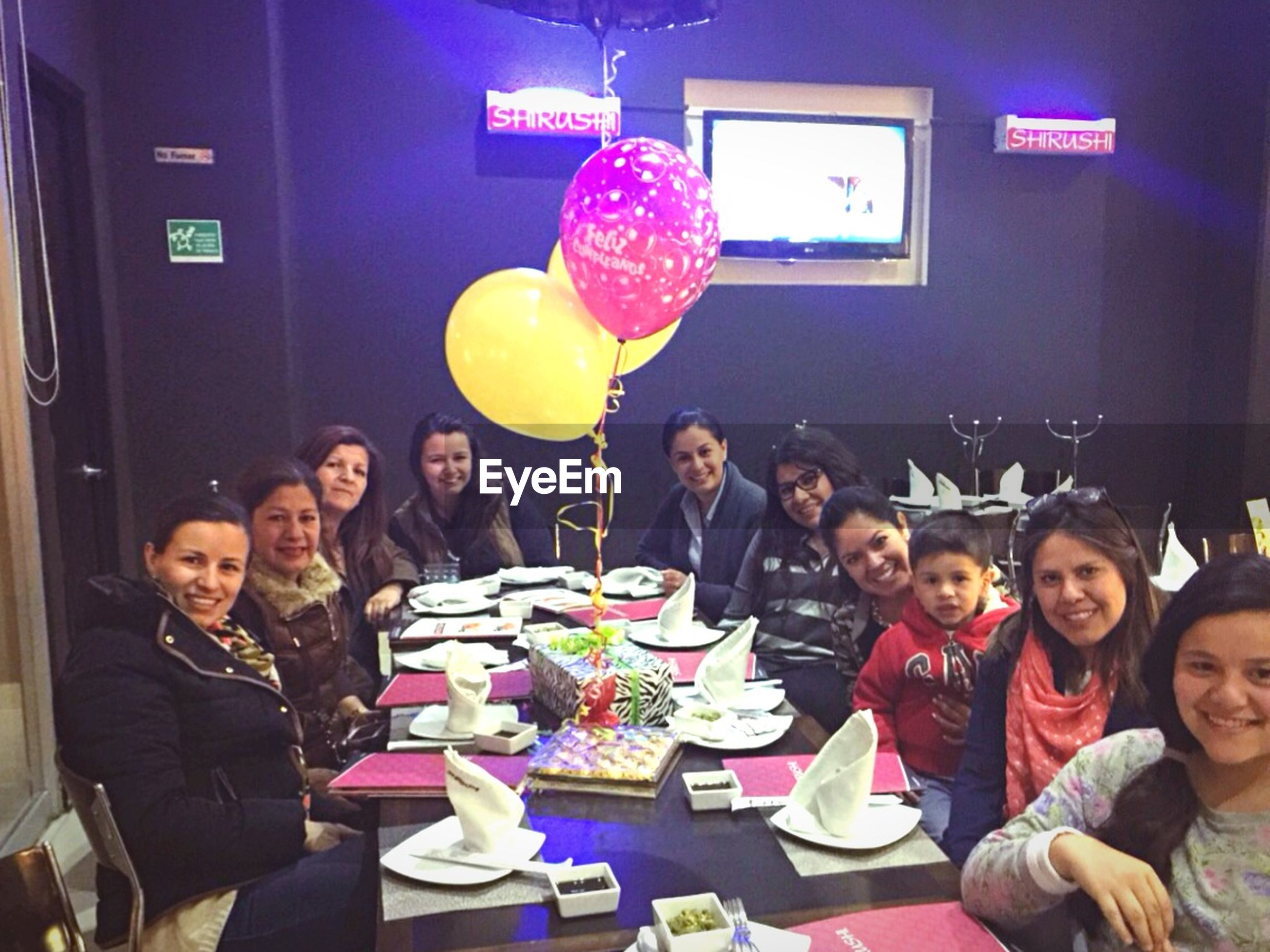 lifestyles, celebration, leisure activity, togetherness, happiness, indoors, illuminated, fun, person, enjoyment, childhood, casual clothing, balloon, smiling, front view, standing, night, elementary age, bonding