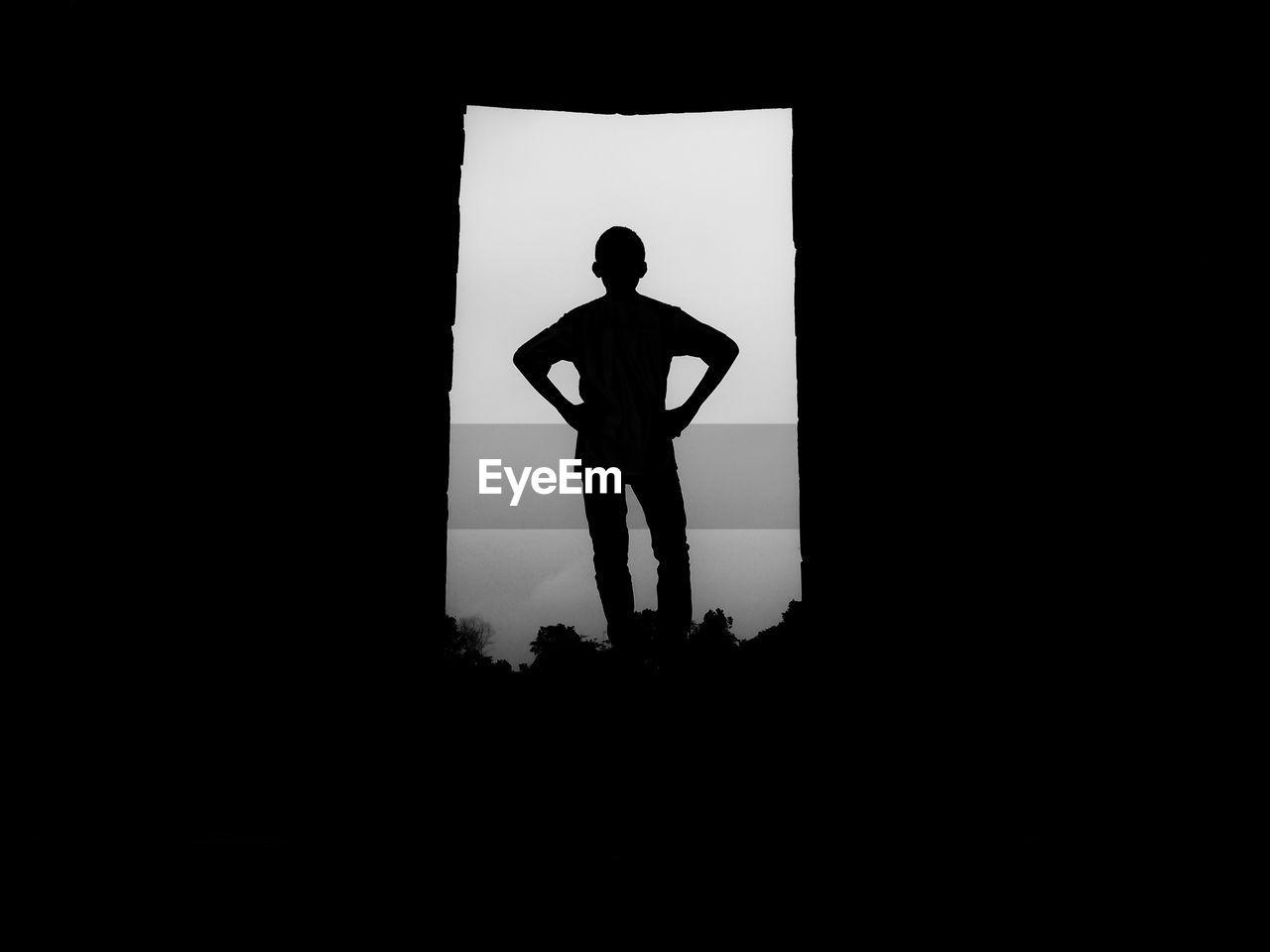 Rear View Of Silhouette Man Standing In Doorway Against Sky
