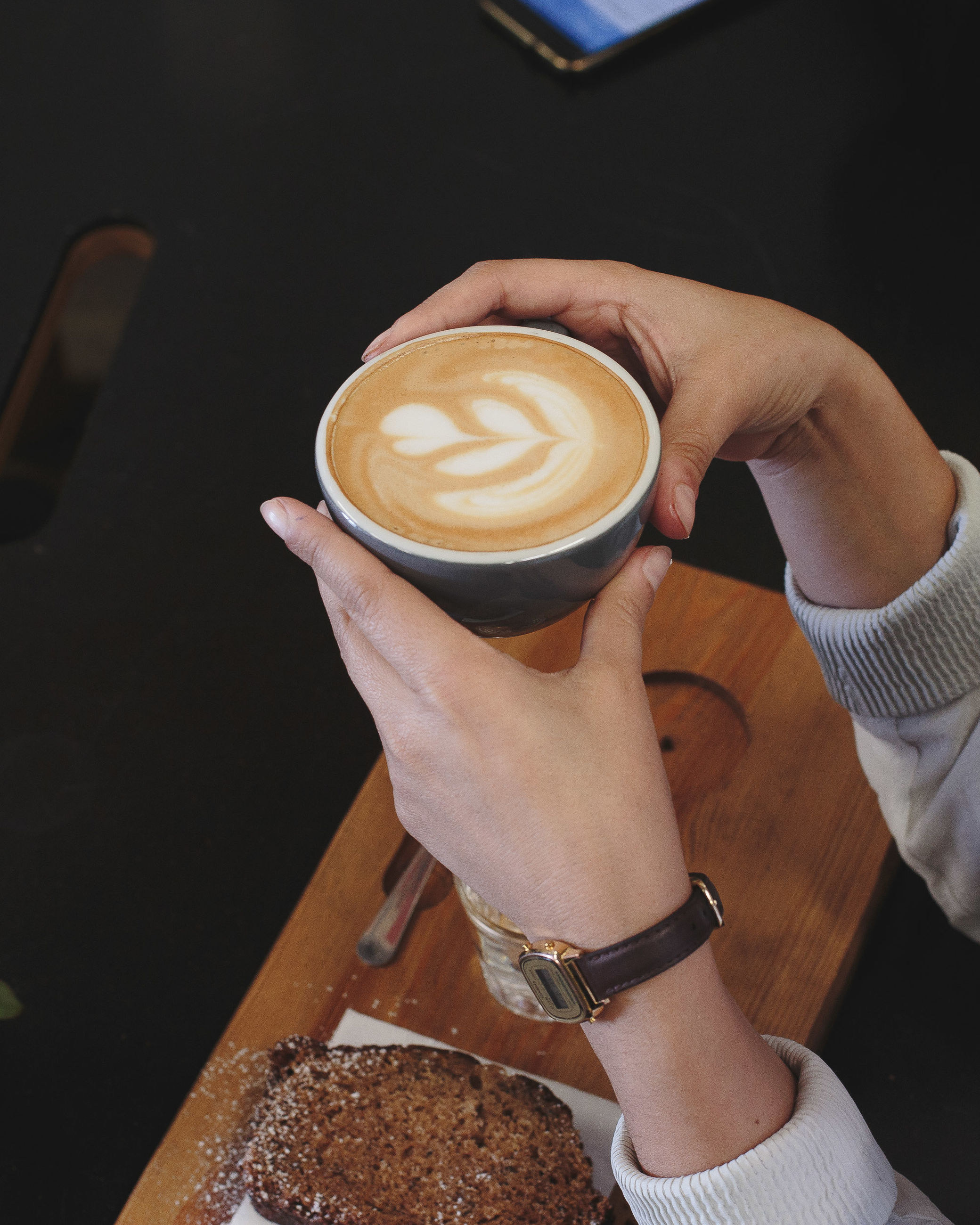 Cropped hand of woman having drink at cafe