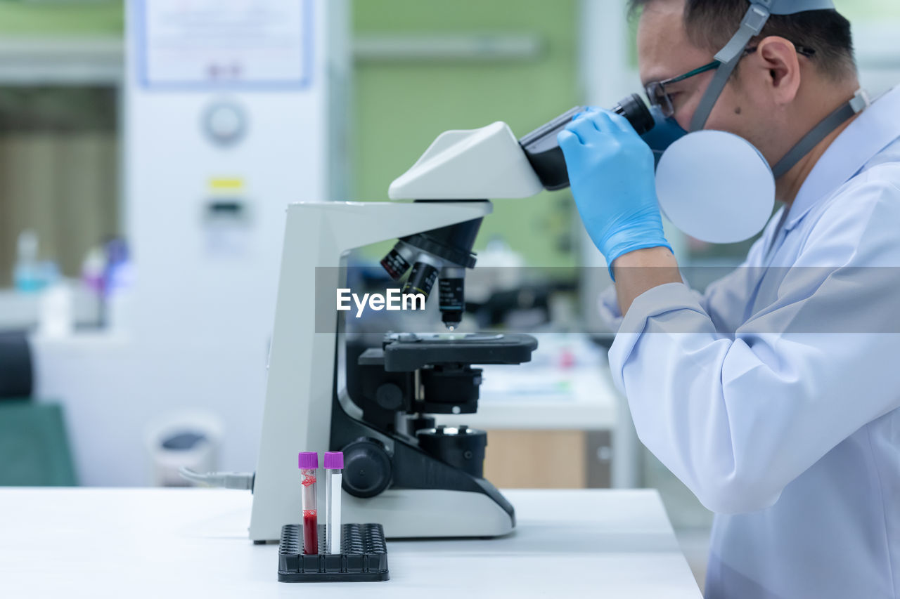 Man working over microscope in laboratory