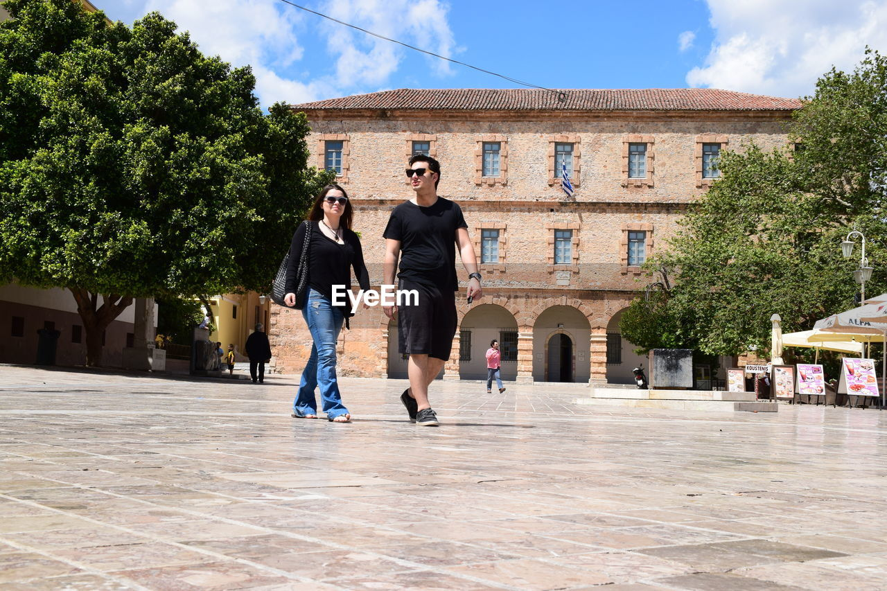 architecture, two people, full length, built structure, young women, real people, young adult, building exterior, togetherness, casual clothing, lifestyles, young men, day, leisure activity, happiness, outdoors, smiling, friendship, sky, tree, bonding, men, city, people
