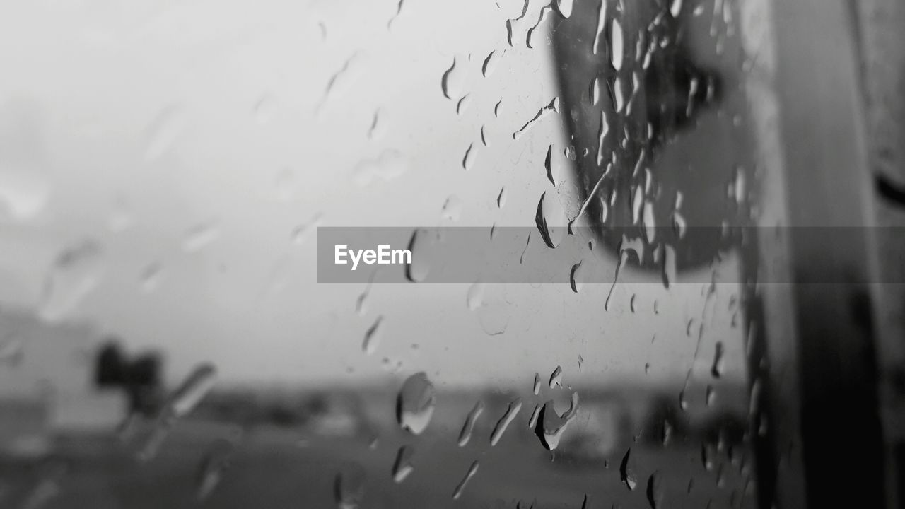 rain, wet, drop, transparent, glass - material, raindrop, rainy season, window, weather, water, close-up, indoors, no people, focus on foreground, day, sky, nature