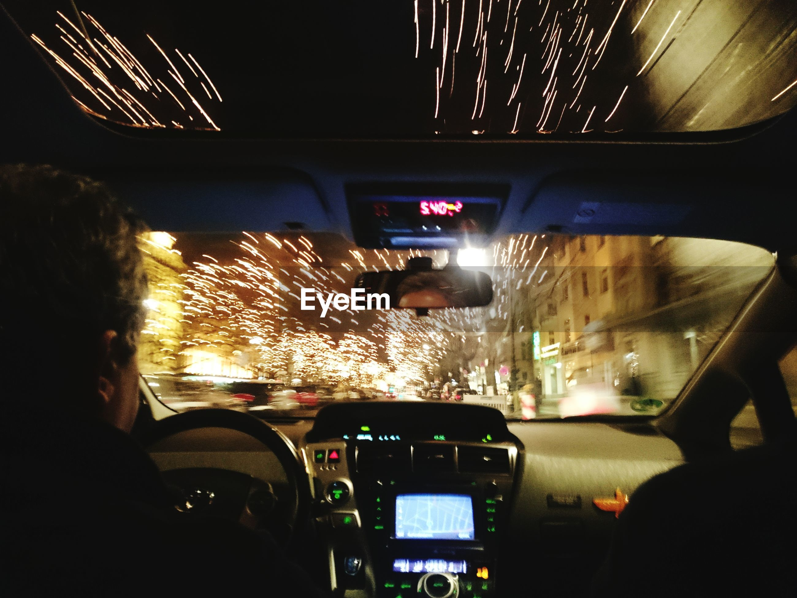 Long exposure of christmas lights seen through windshield in city