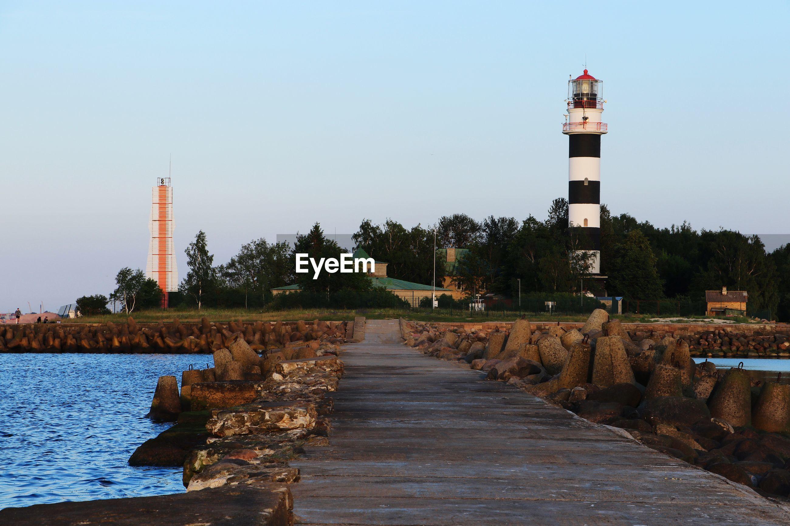 Lighthouse amidst buildings against clear sky