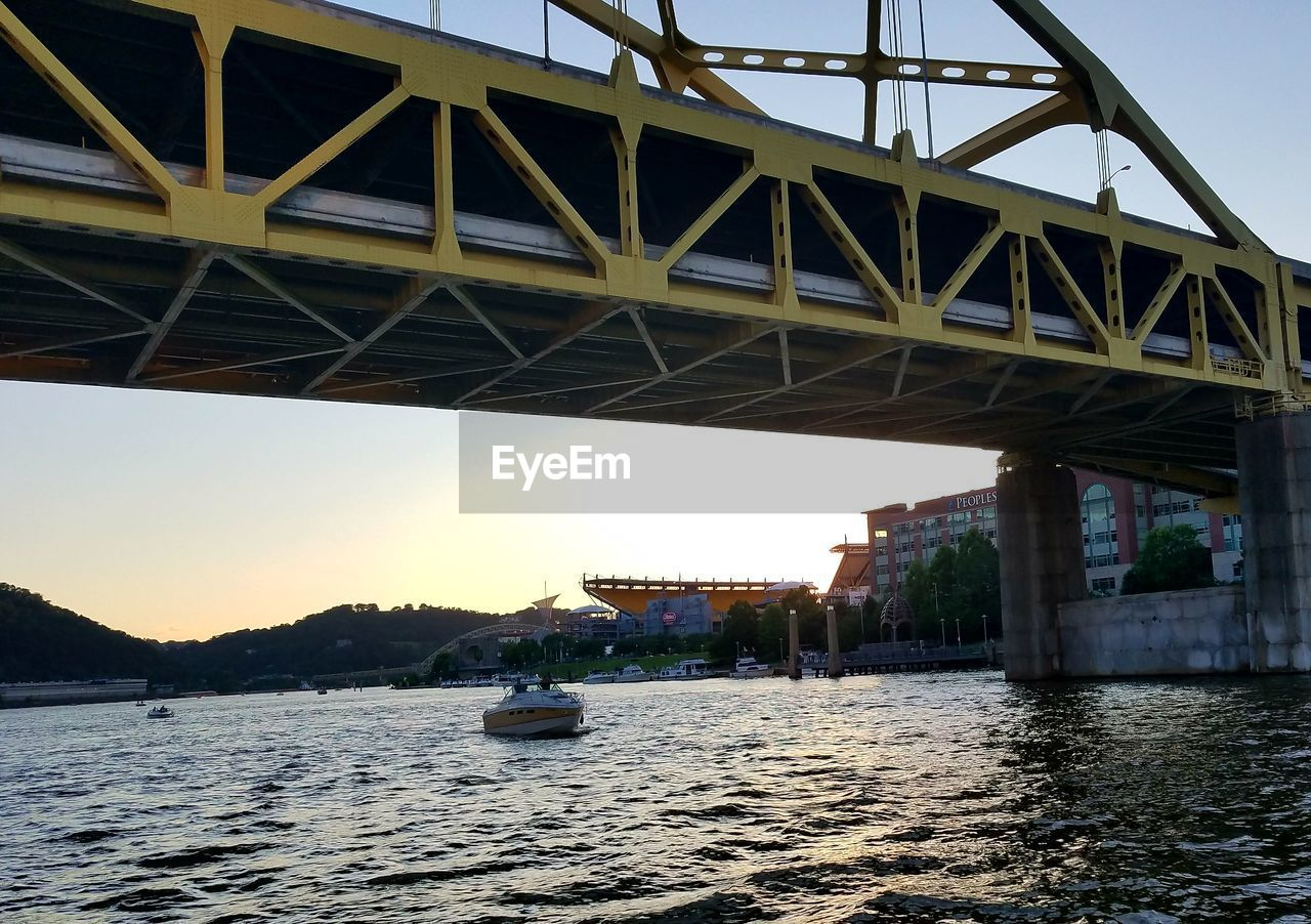 bridge - man made structure, connection, transportation, architecture, engineering, river, built structure, water, waterfront, outdoors, mode of transport, bridge, sky, day, no people, travel destinations, nautical vessel, city, underneath, nature