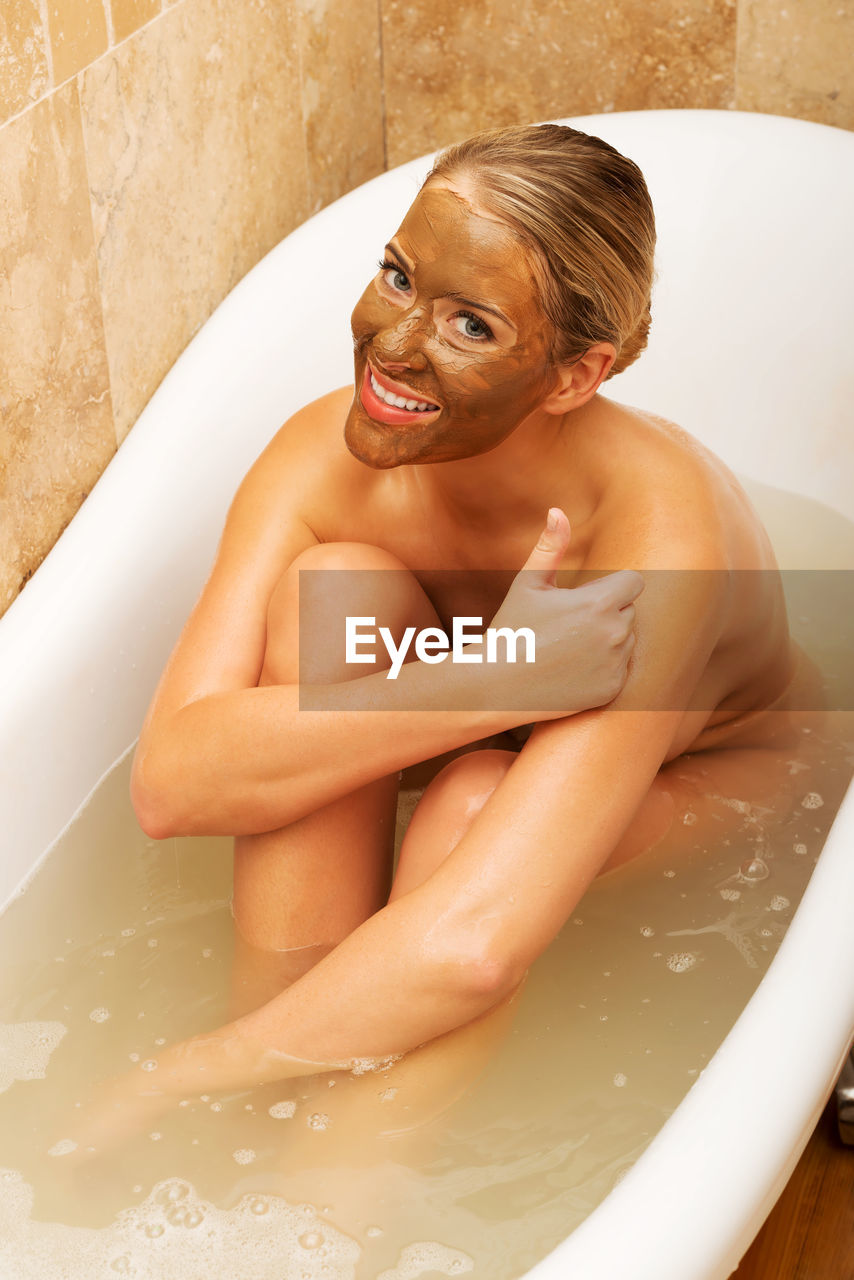 High Angle Portrait Of Naked Young Woman With Facial Mask Sitting In Bathtub