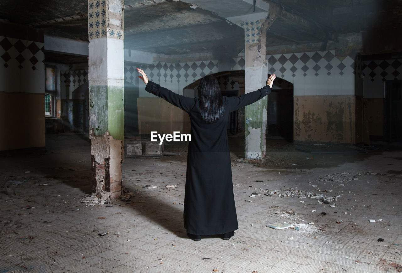 Rear view of woman with arms outstretched standing in abandoned building