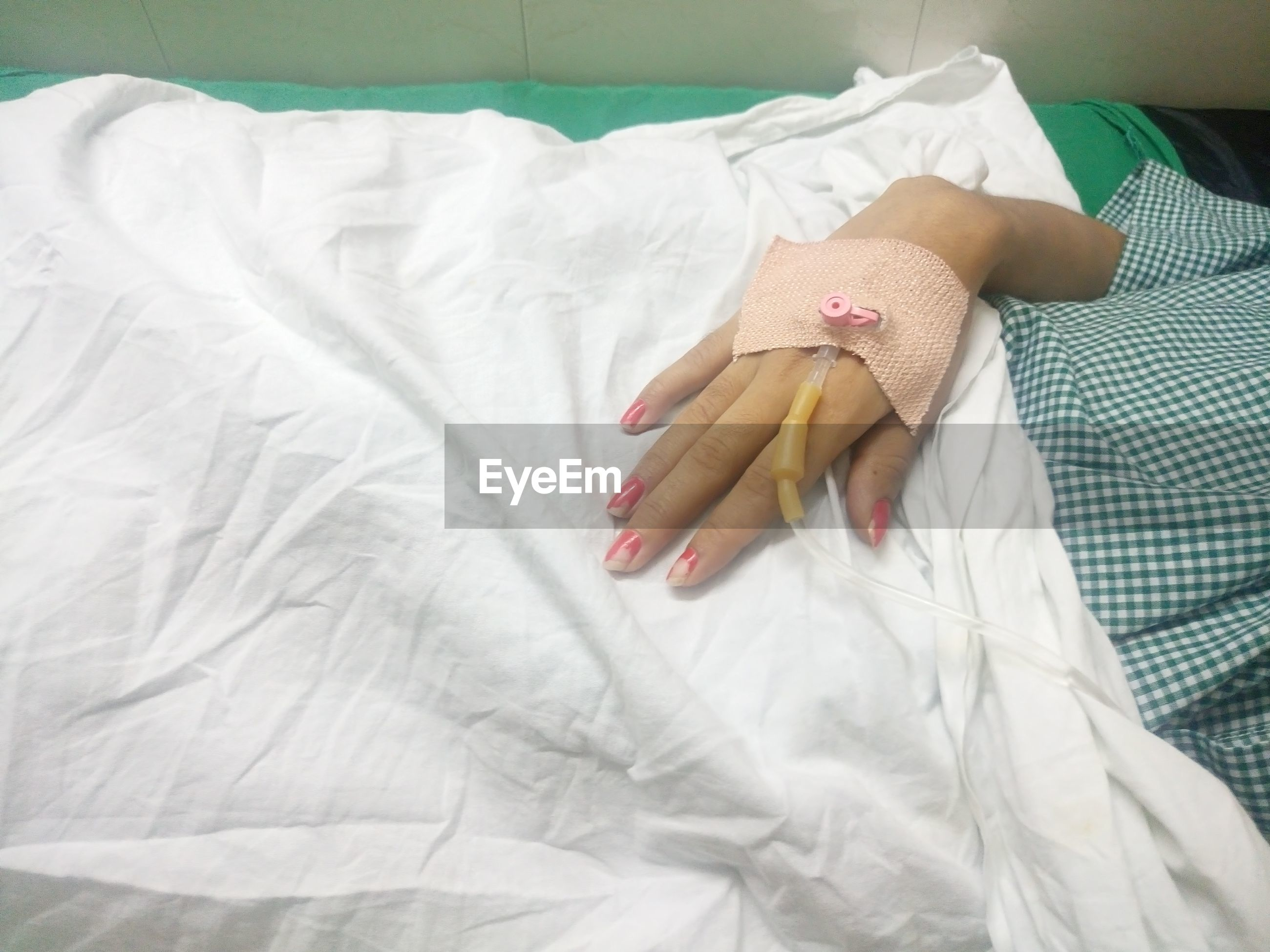 Cropped image of woman with iv drip on hand at hospital