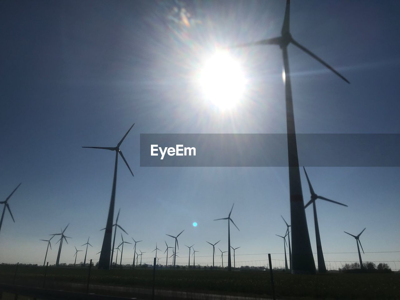 fuel and power generation, renewable energy, environmental conservation, wind turbine, alternative energy, sun, wind power, turbine, sky, environment, sunlight, nature, low angle view, lens flare, sunbeam, field, beauty in nature, sunny, land, no people, outdoors, bright, sustainable resources, brightly lit