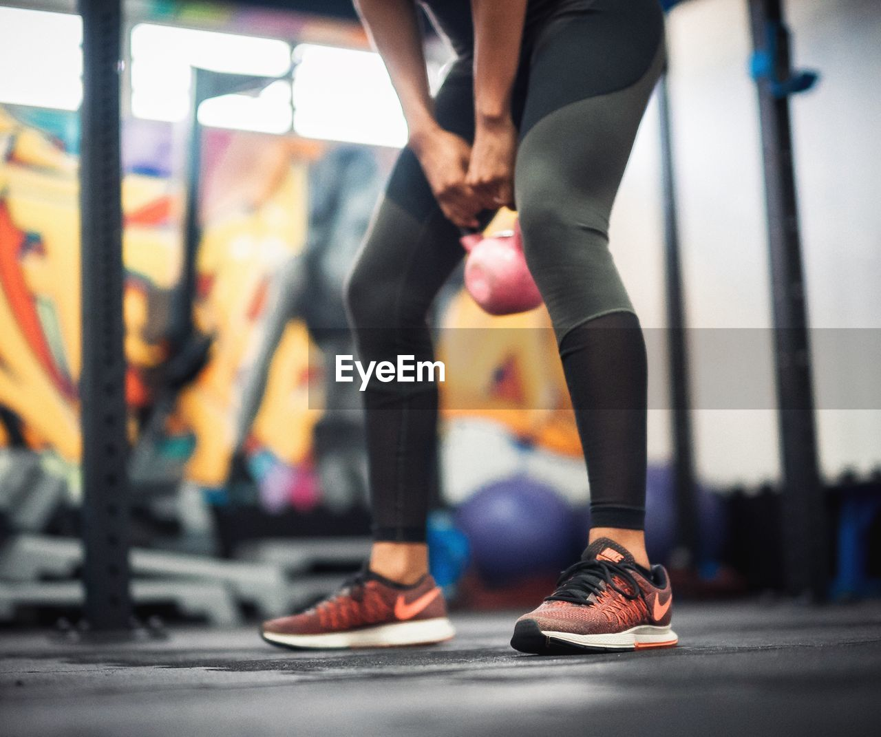 Low Section Of Young Woman Lifting Kettlebell At Gym