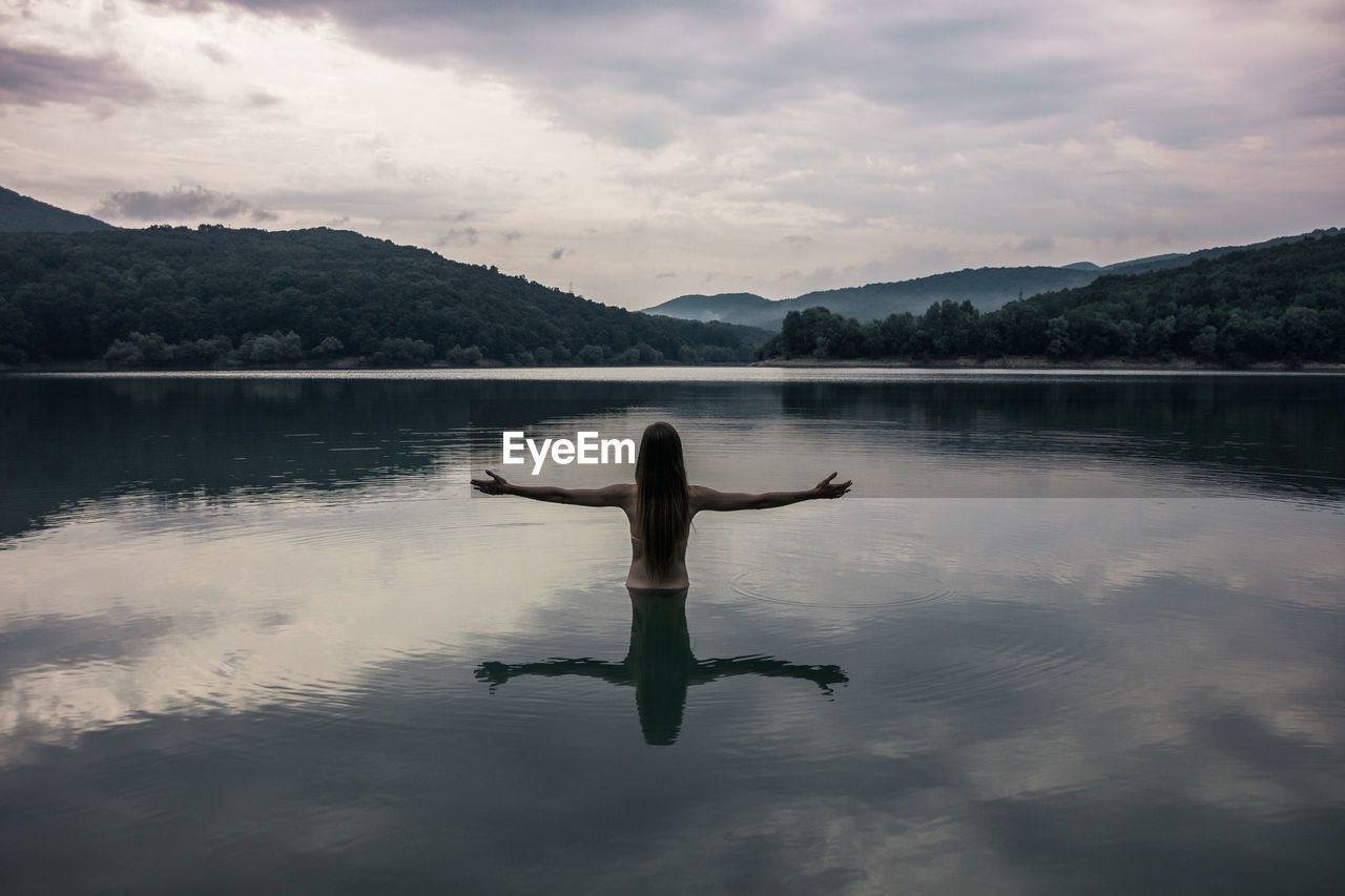 Rear View Of Woman With Arms Outstretched In Lake Against Mountains