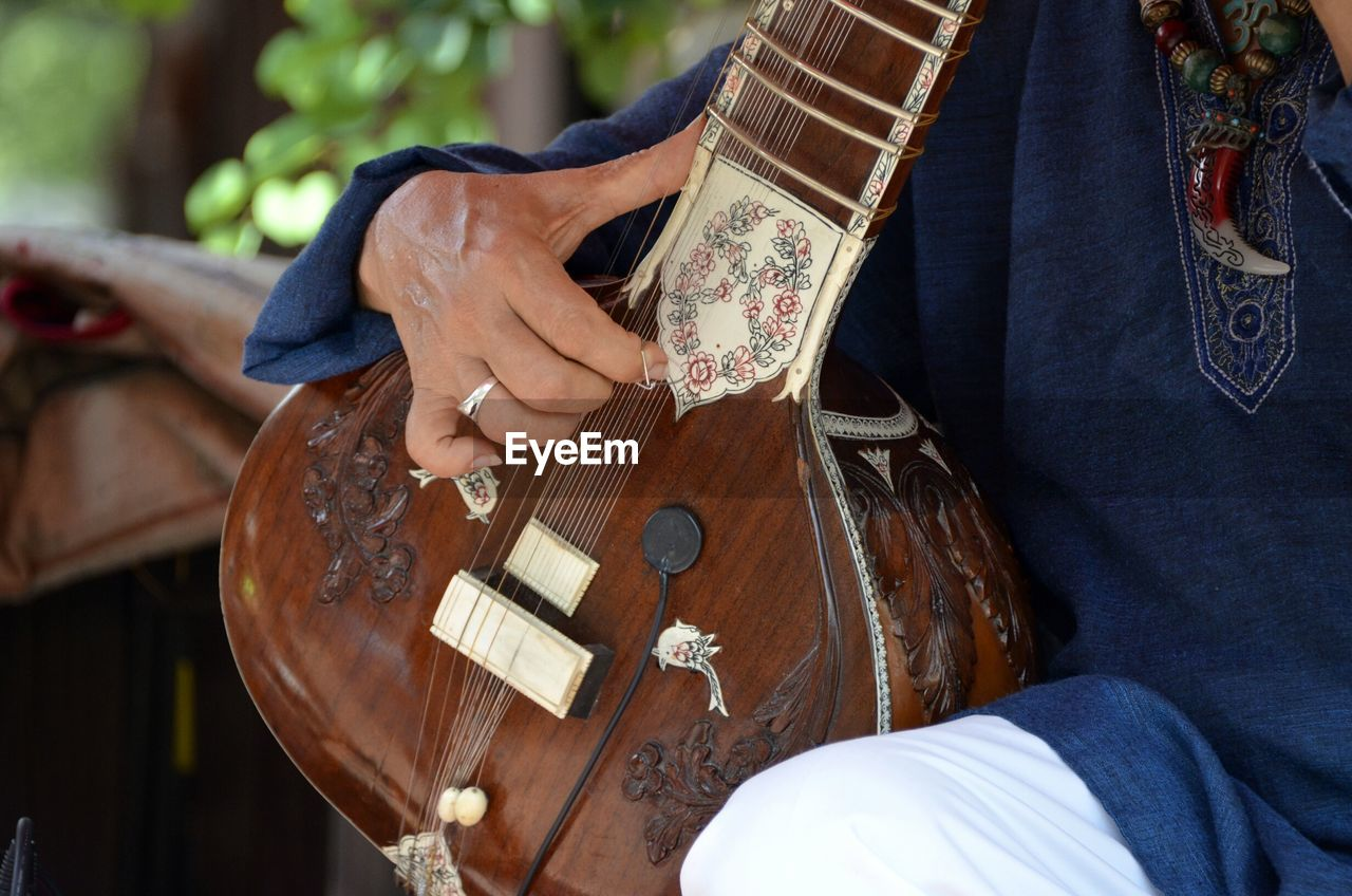 Midsection of man playing sitar