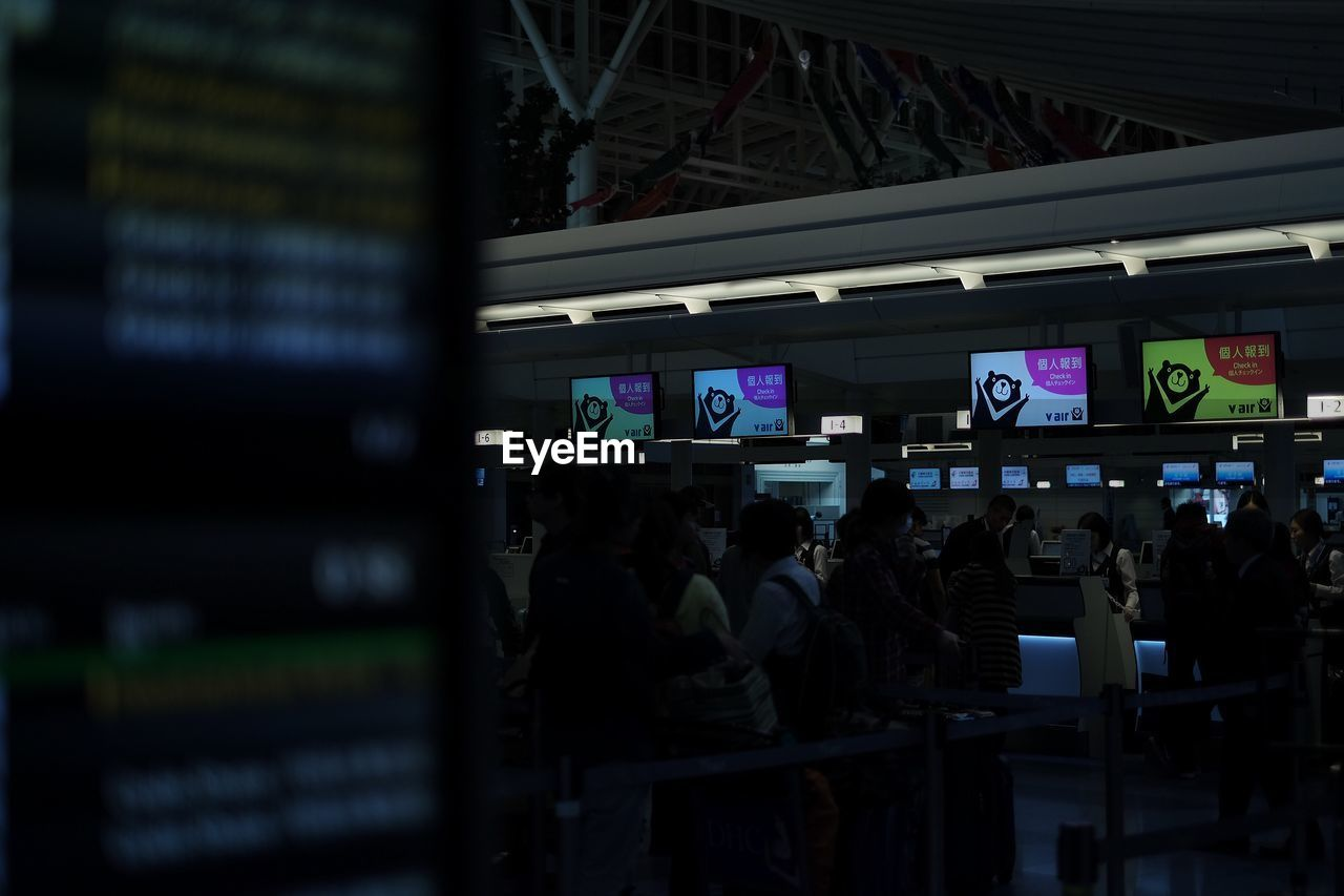 text, communication, night, store, real people, retail, device screen, indoors, large group of people, men, supermarket, people