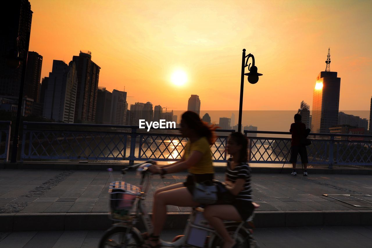 sunset, city, architecture, built structure, building exterior, bicycle, real people, transportation, skyscraper, bridge - man made structure, mode of transport, city life, outdoors, urban skyline, travel, lifestyles, men, riding, full length, cityscape, leisure activity, sky, land vehicle, women, travel destinations, water, one person, day, people