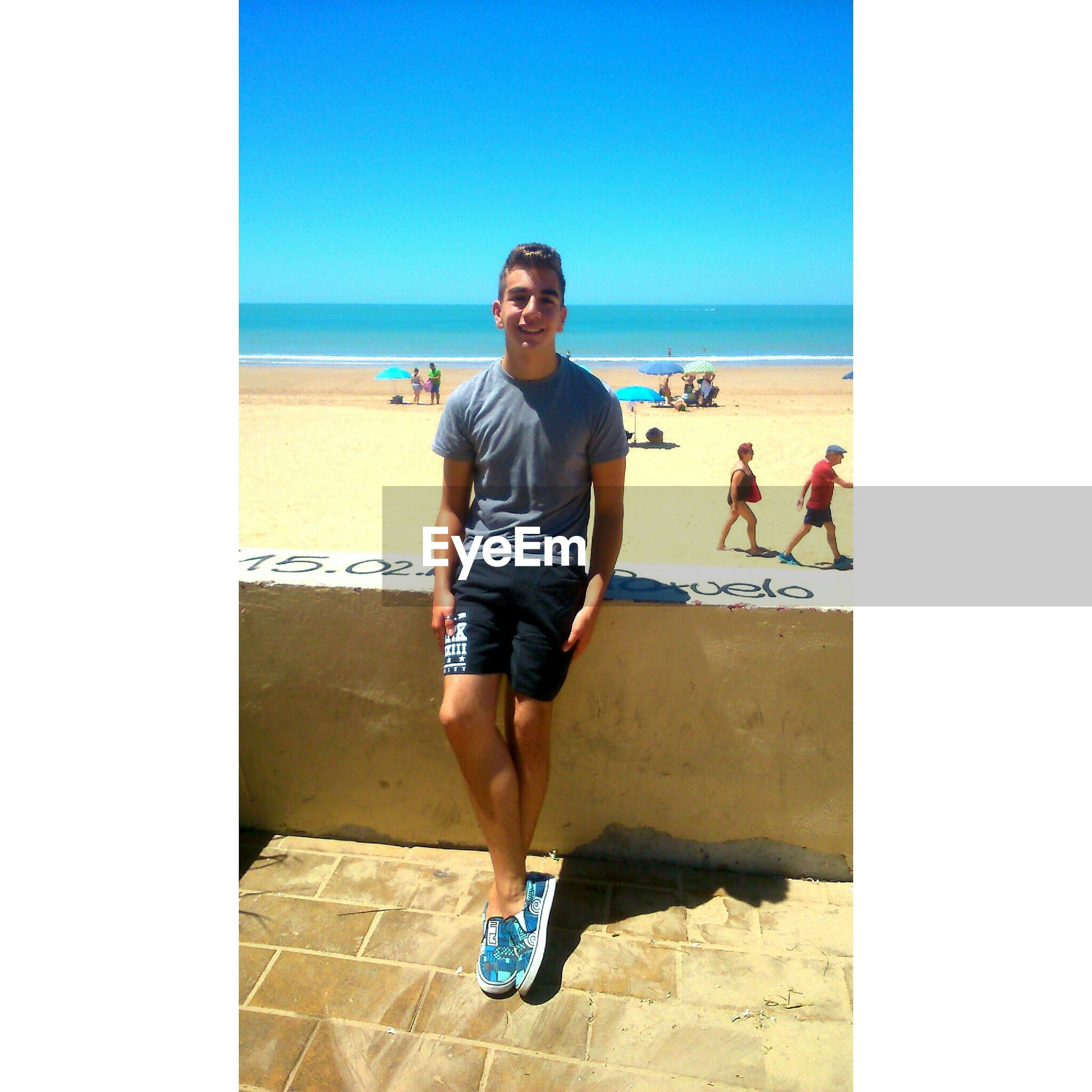 sea, horizon over water, clear sky, lifestyles, beach, leisure activity, copy space, young adult, transfer print, person, water, full length, casual clothing, shore, standing, looking at camera, auto post production filter, portrait
