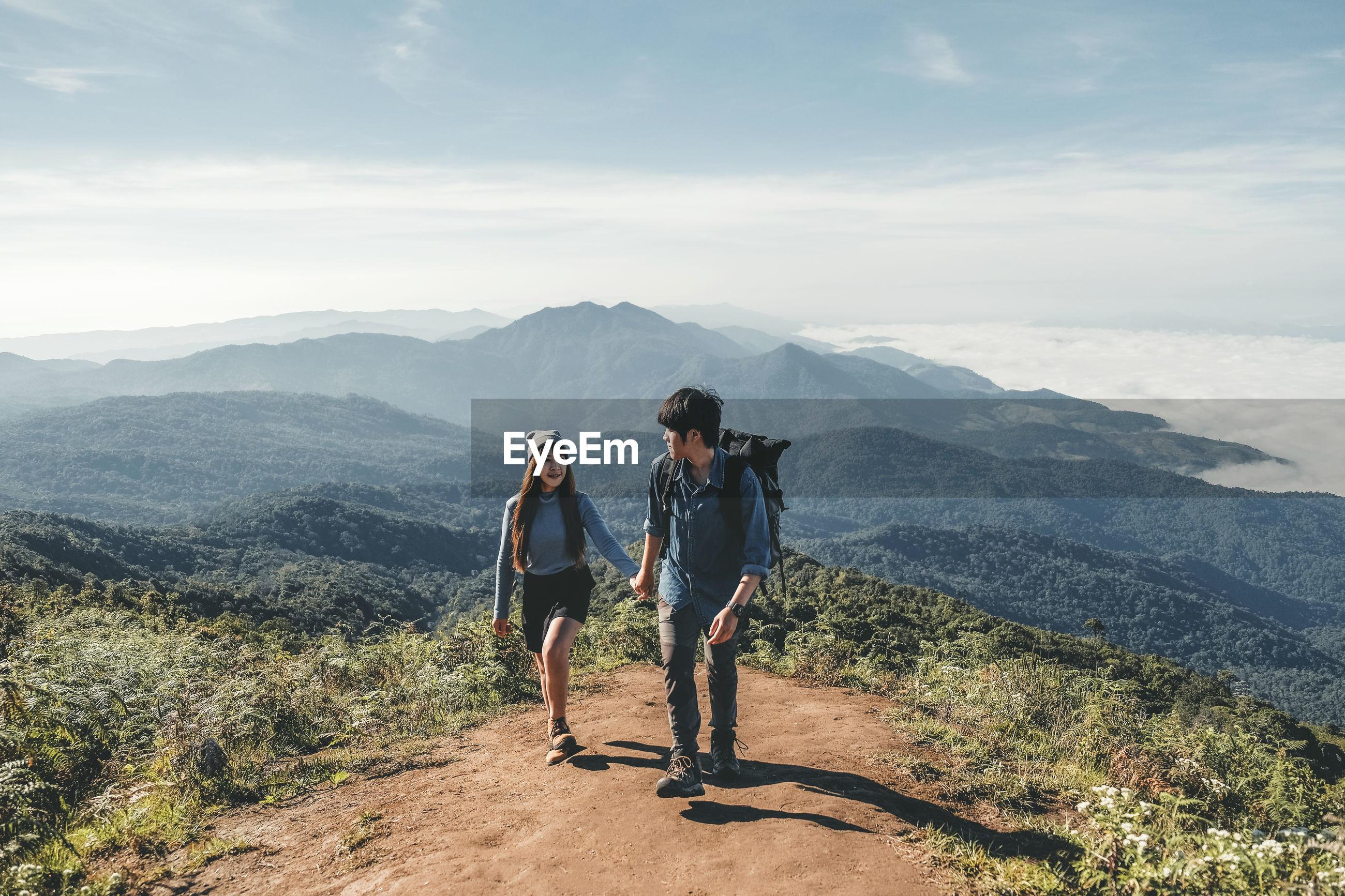 Couple on mountain against sky