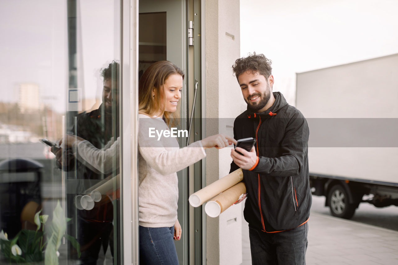 YOUNG COUPLE STANDING ON GLASS WINDOW IN OFFICE