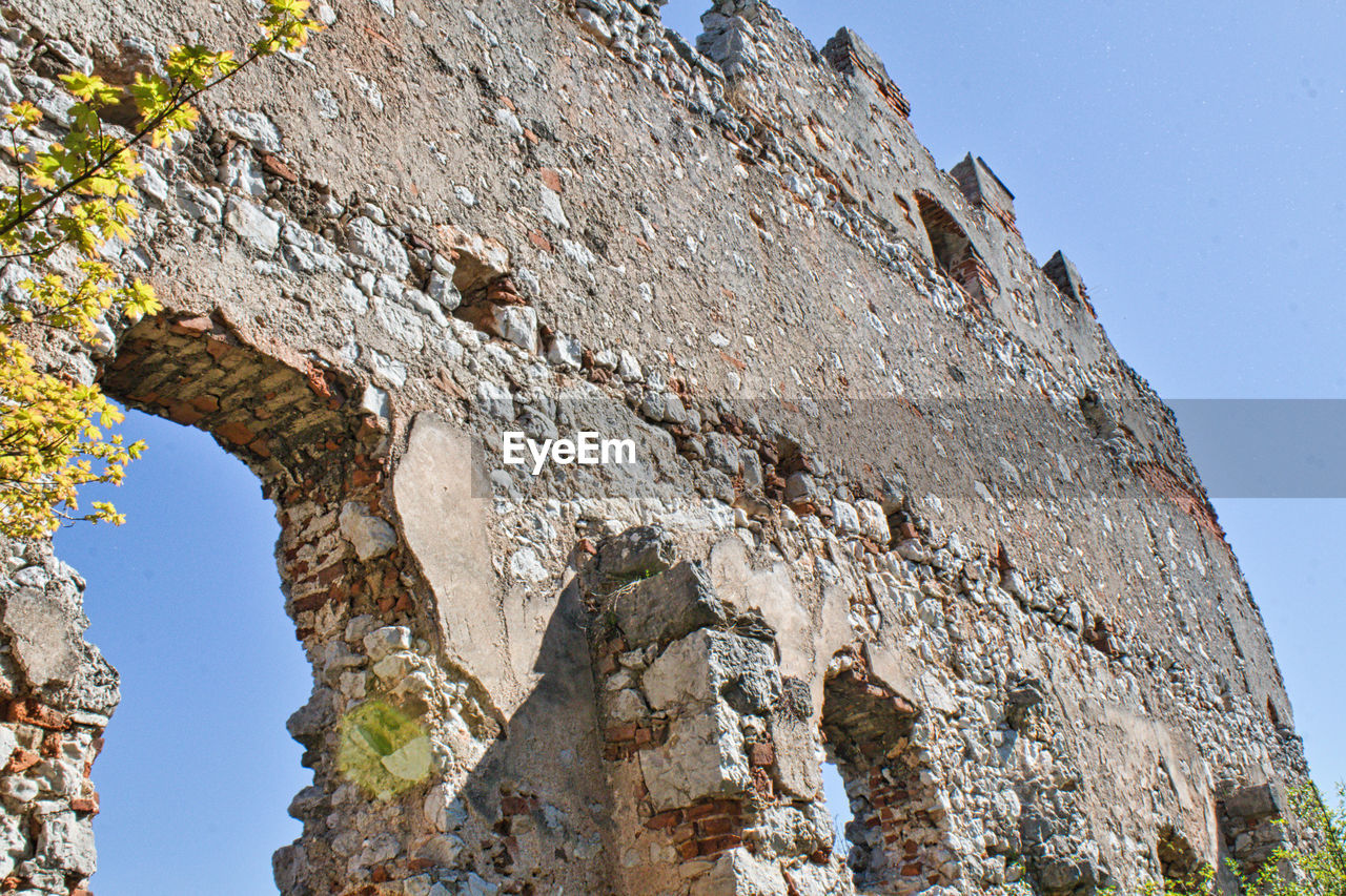 low angle view, sky, clear sky, rock, day, nature, solid, rock - object, no people, rock formation, architecture, history, outdoors, sunlight, the past, arch, weathered, damaged, built structure, old ruin, ruined, formation, ancient civilization