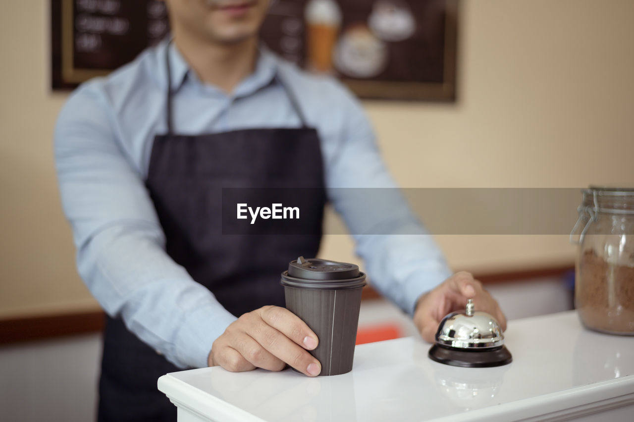 MIDSECTION OF MAN WORKING WITH COFFEE IN CAFE