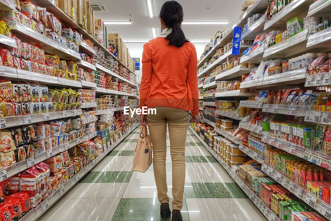 retail, shopping, store, choice, supermarket, consumerism, food and drink, standing, indoors, lifestyles, rear view, one person, variation, abundance, full length, customer, adult, food, women, decisions, aisle, groceries, hairstyle