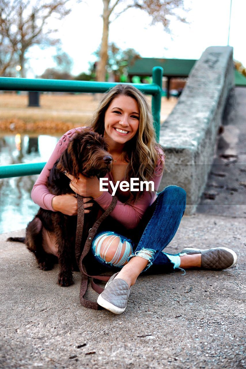 Portrait of smiling young woman sitting with dog on footpath